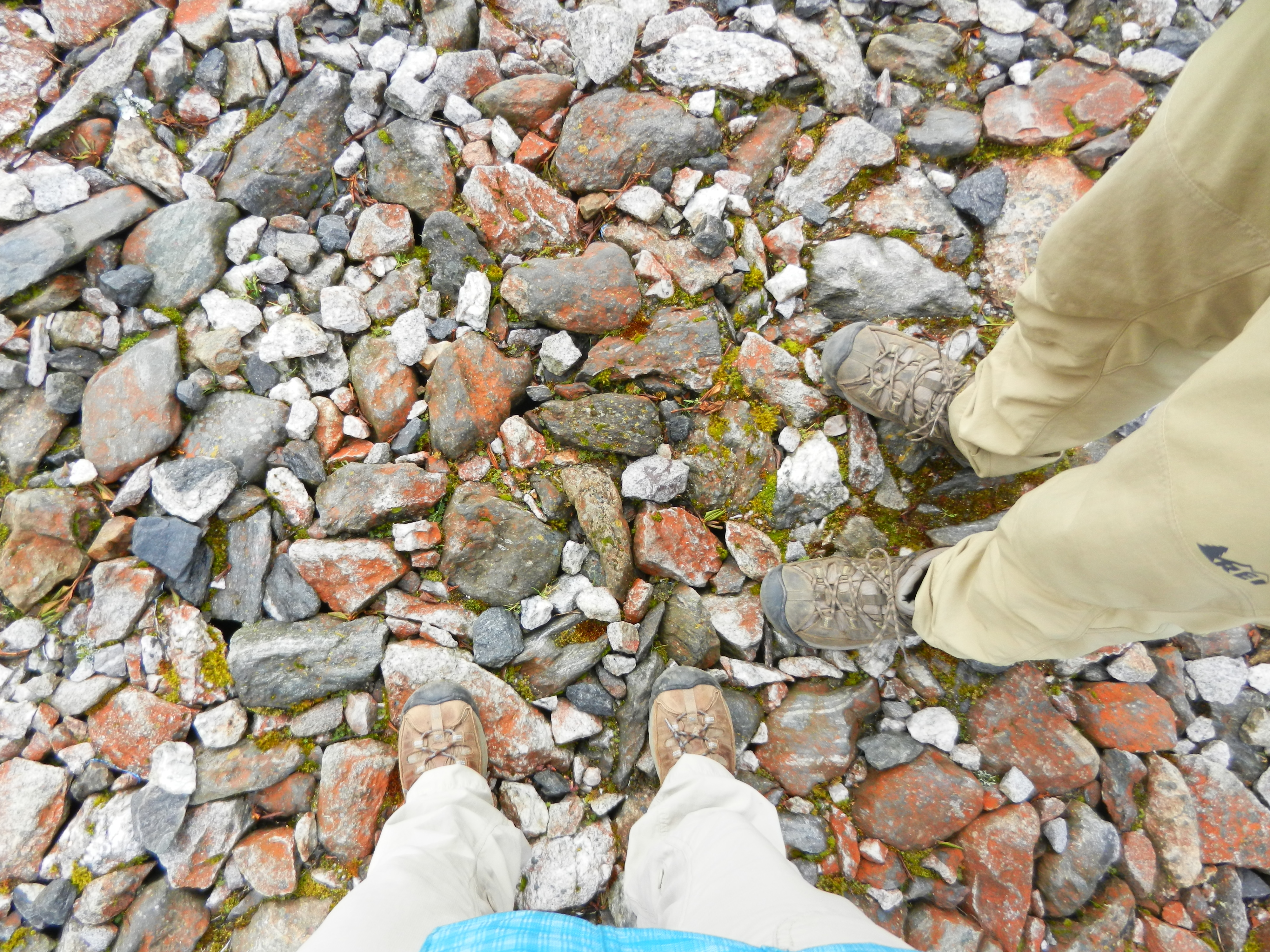 View of two people's feet wearing hiking boots and standing on multicolored rocks