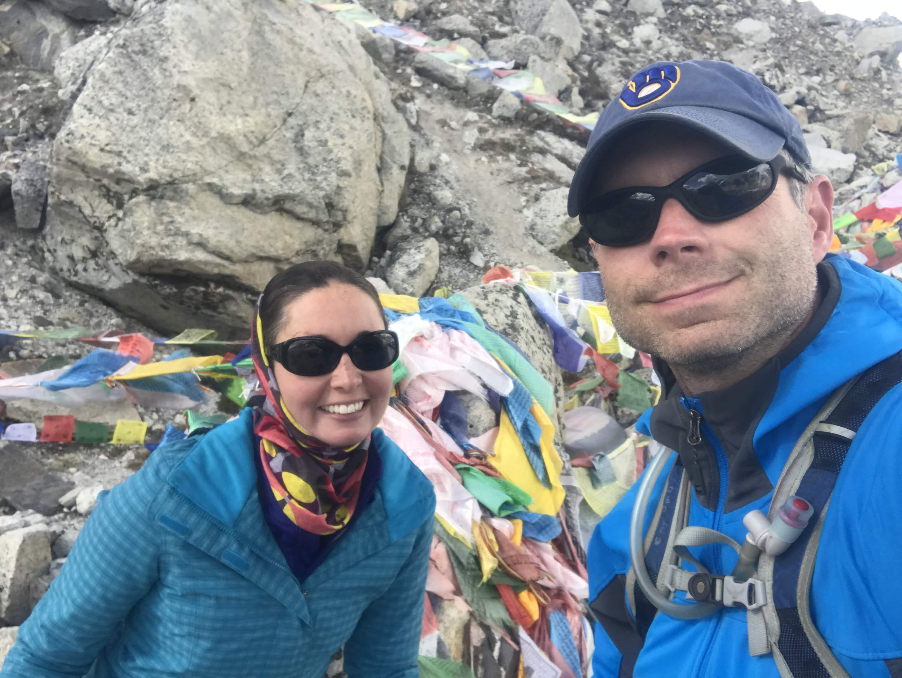 Young couple standing in front of a pile of prayer flags