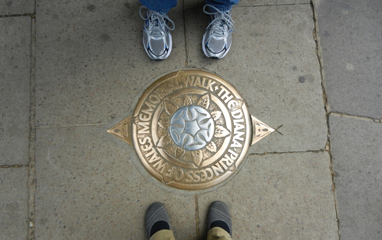 """Woman's feet wearing black socks and grey shoes at the bottom of the photo, men's feet wearing tennis shoes at the top of the photo, with a gold colored medallion in the middle that reads """"The Diana, Princess of Wales, Memorial Walk""""."""
