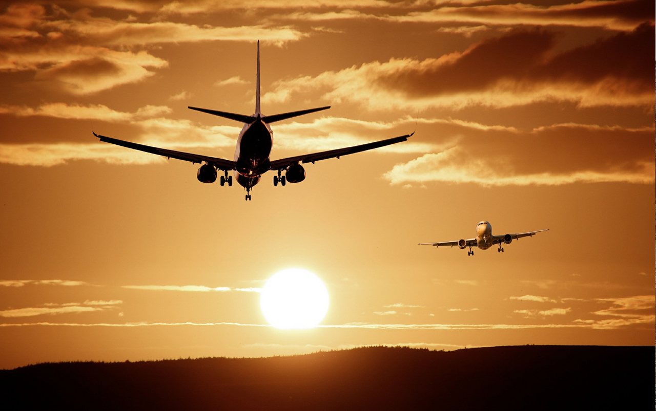 Two airplanes flying opposite directions through a golden colored sky