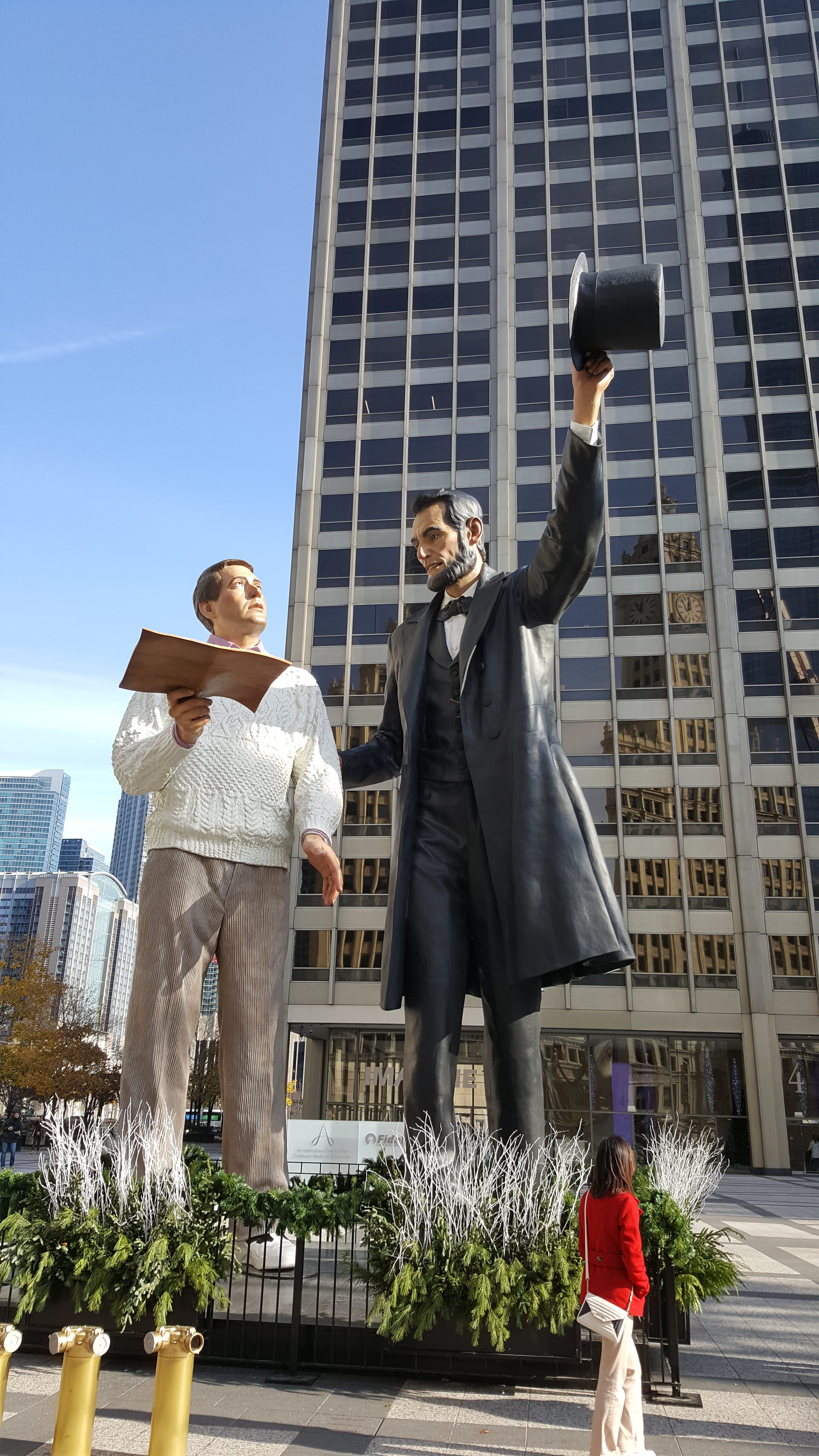 Statue of two men in front of a skyscraper
