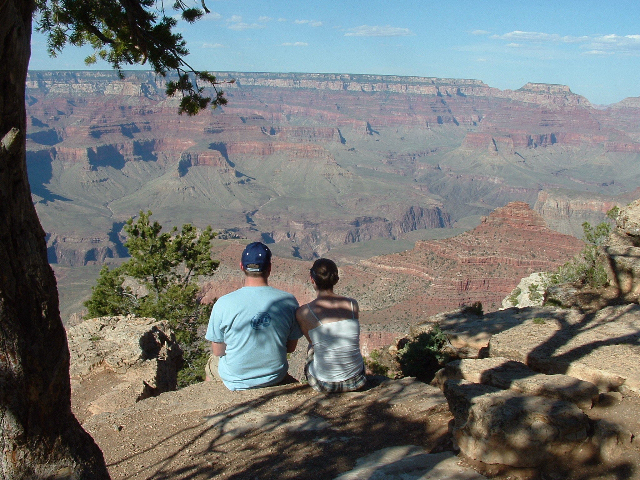 Couple sitting on edge of the Grand Canyon with their backs to the camera.