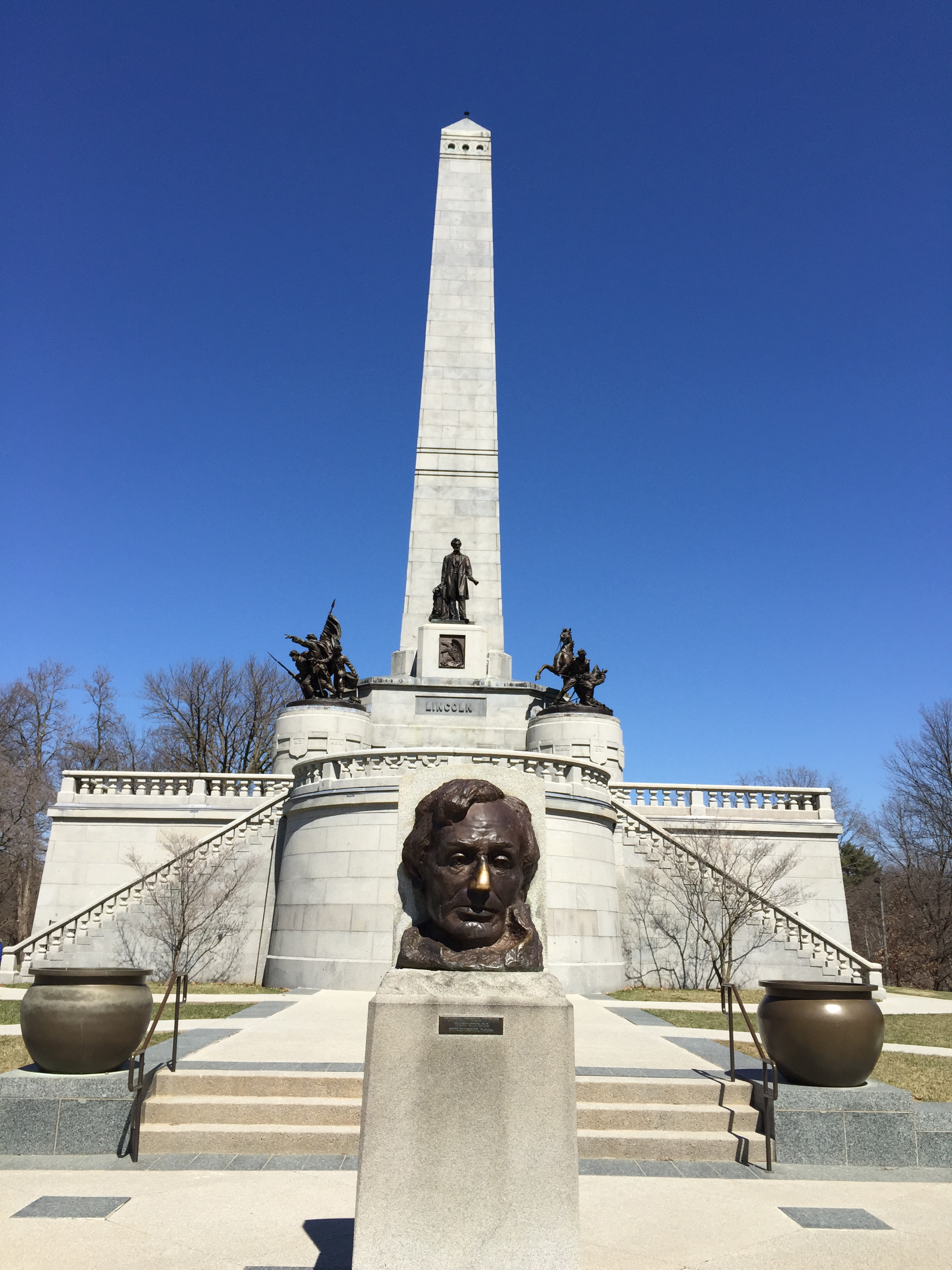Tomb monument in background, bust of Abraham Lincoln in foreground