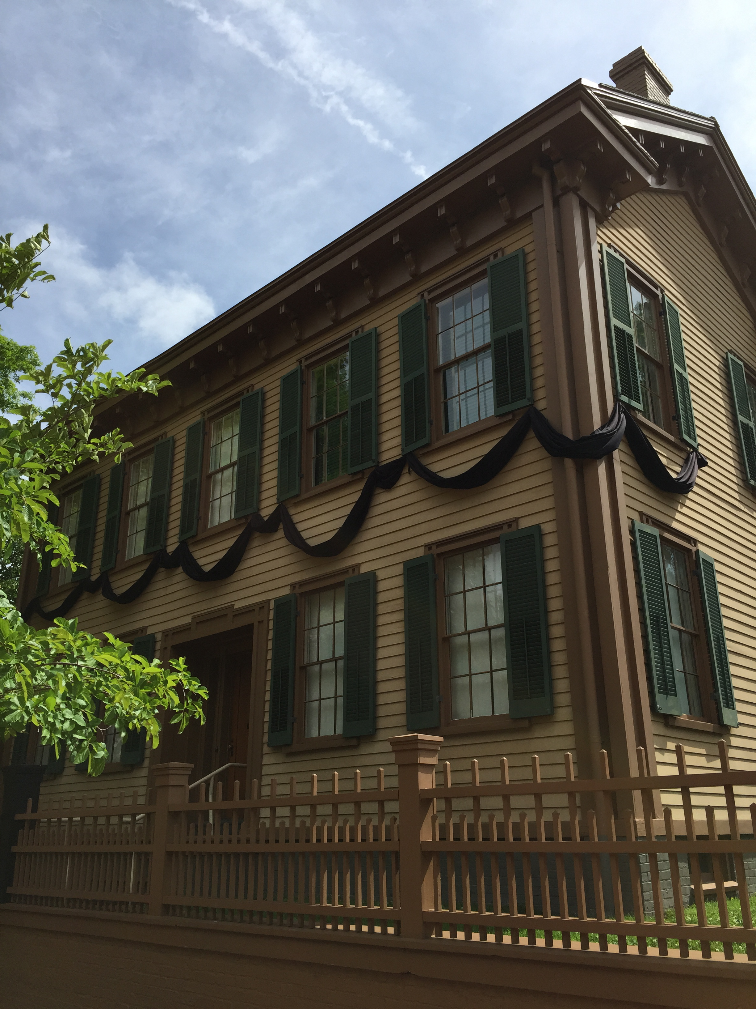 Two-story brown home with green shutters
