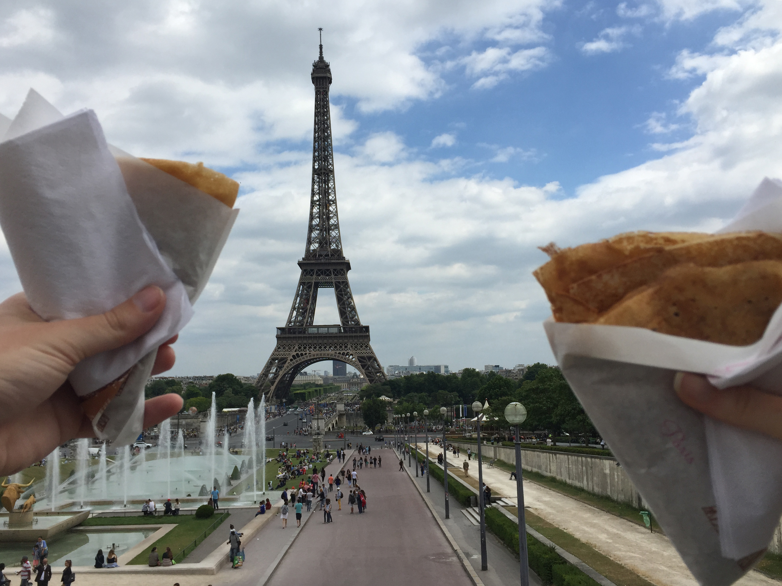 Two crepes held up in the foreground with the Eiffel Tower in the background.