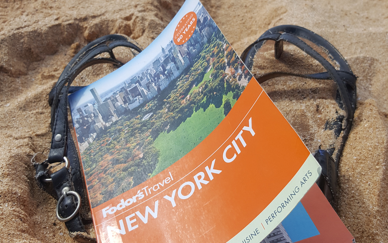 New York City guide book resting on black sandals on a sandy beach.