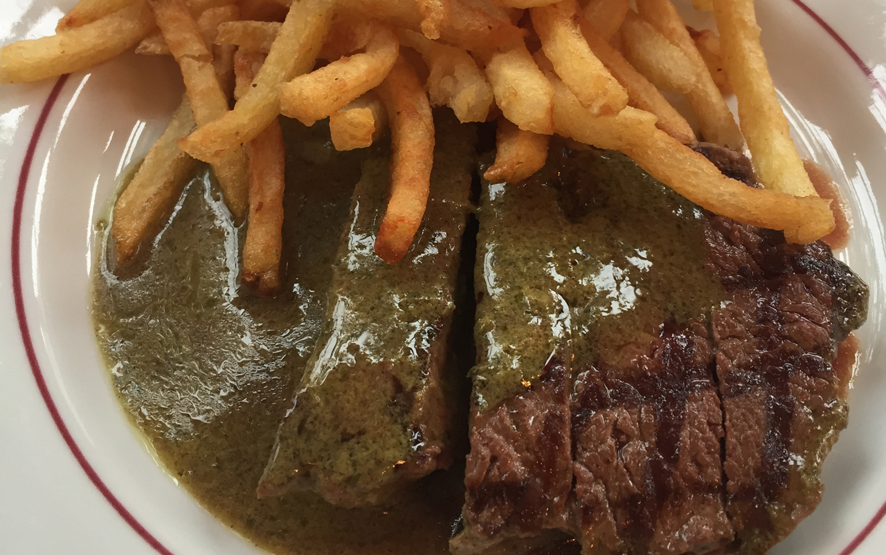 Steak and fries with green sauce.