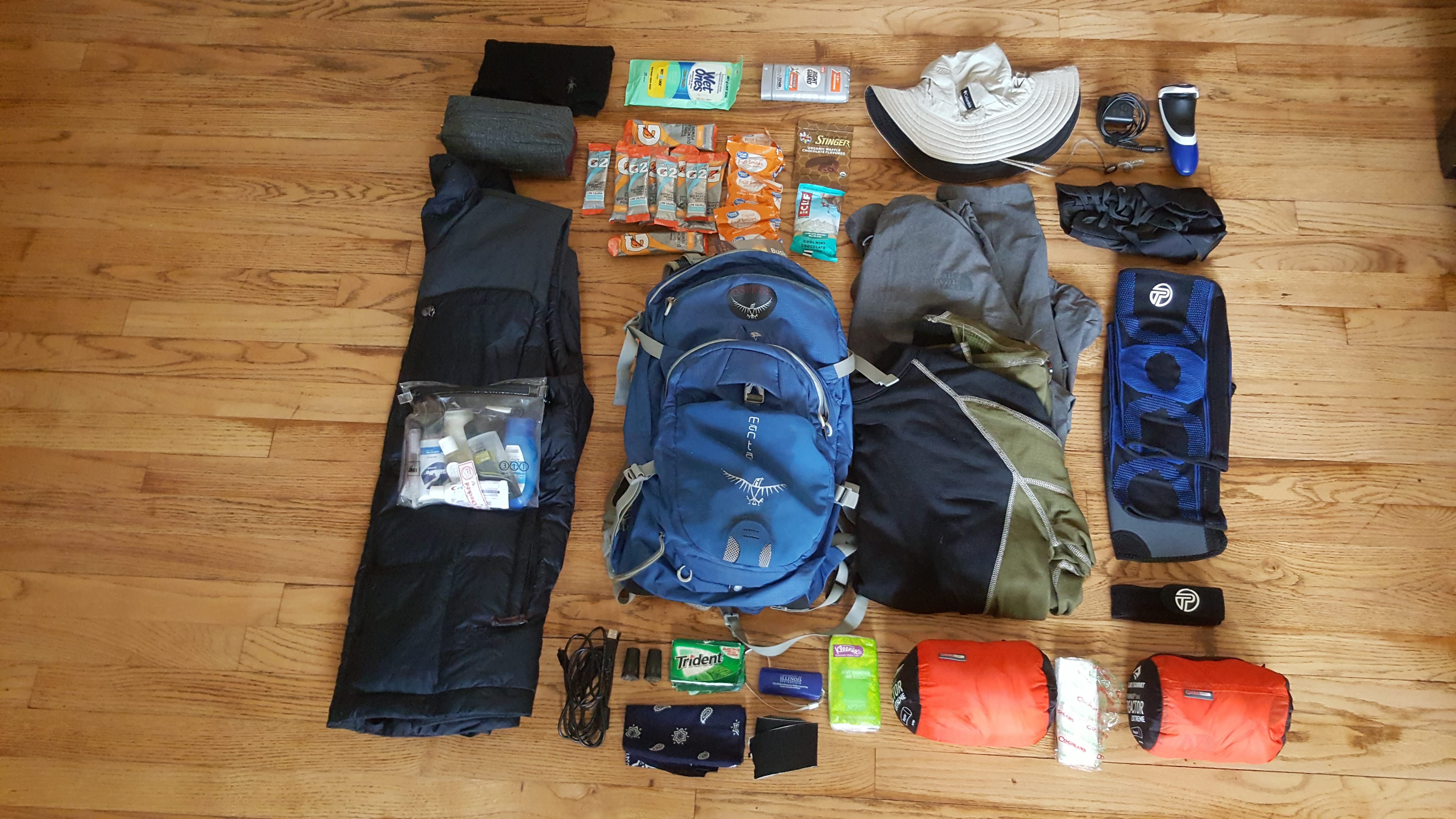 Small blue backpack laid out on floor with items unpacked and surrounding it in an orderly fashion.