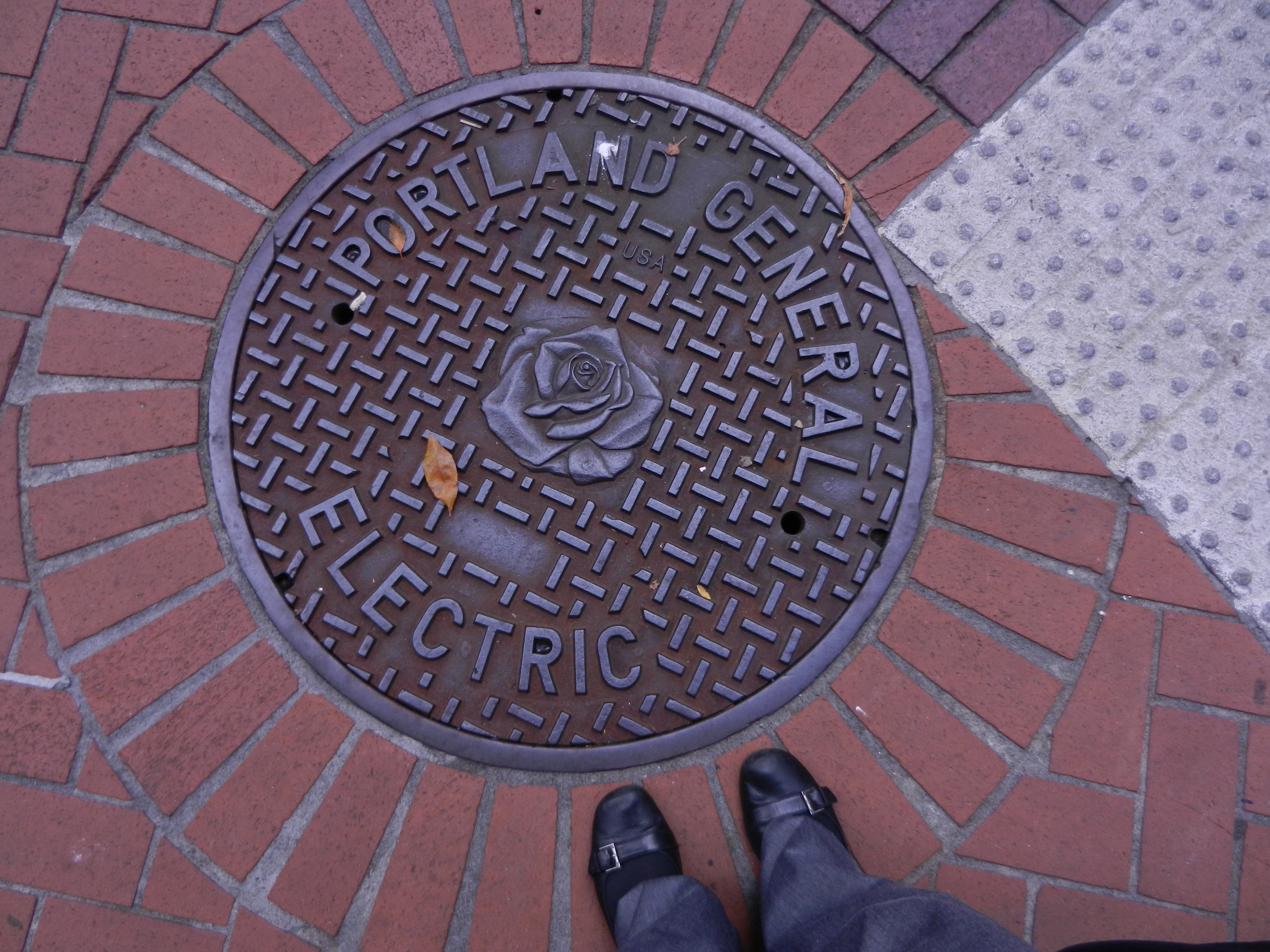 Portland General Electric manhole cover with a rose on it, and feet standing next to it.