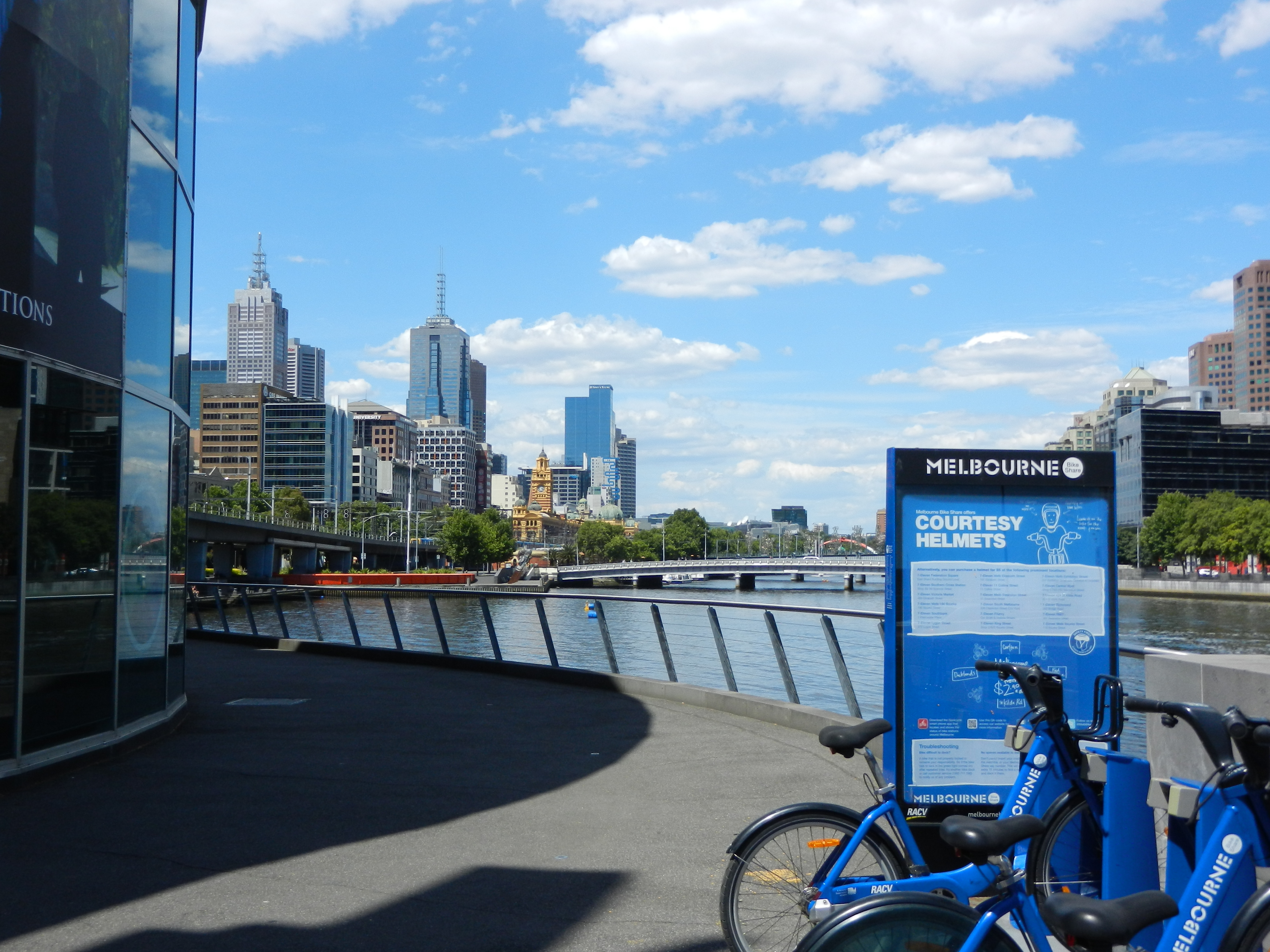 Blue bicycles in the foreground with a river and the Melbourne, Australia skyline in the background.
