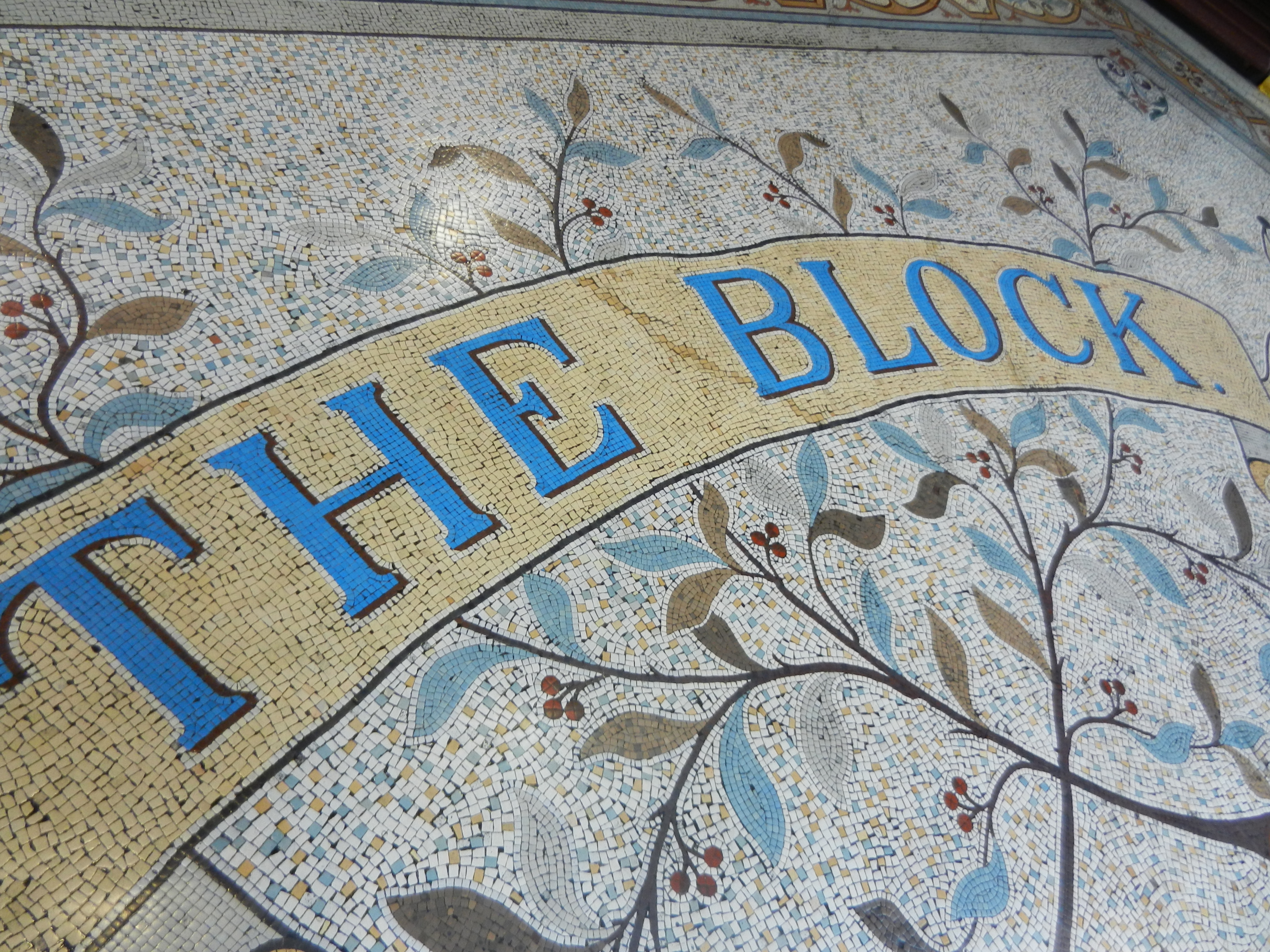 """Mosaic tiled sidewalk that reads """"The Block Arcade"""" in blue letters on a yellow background."""