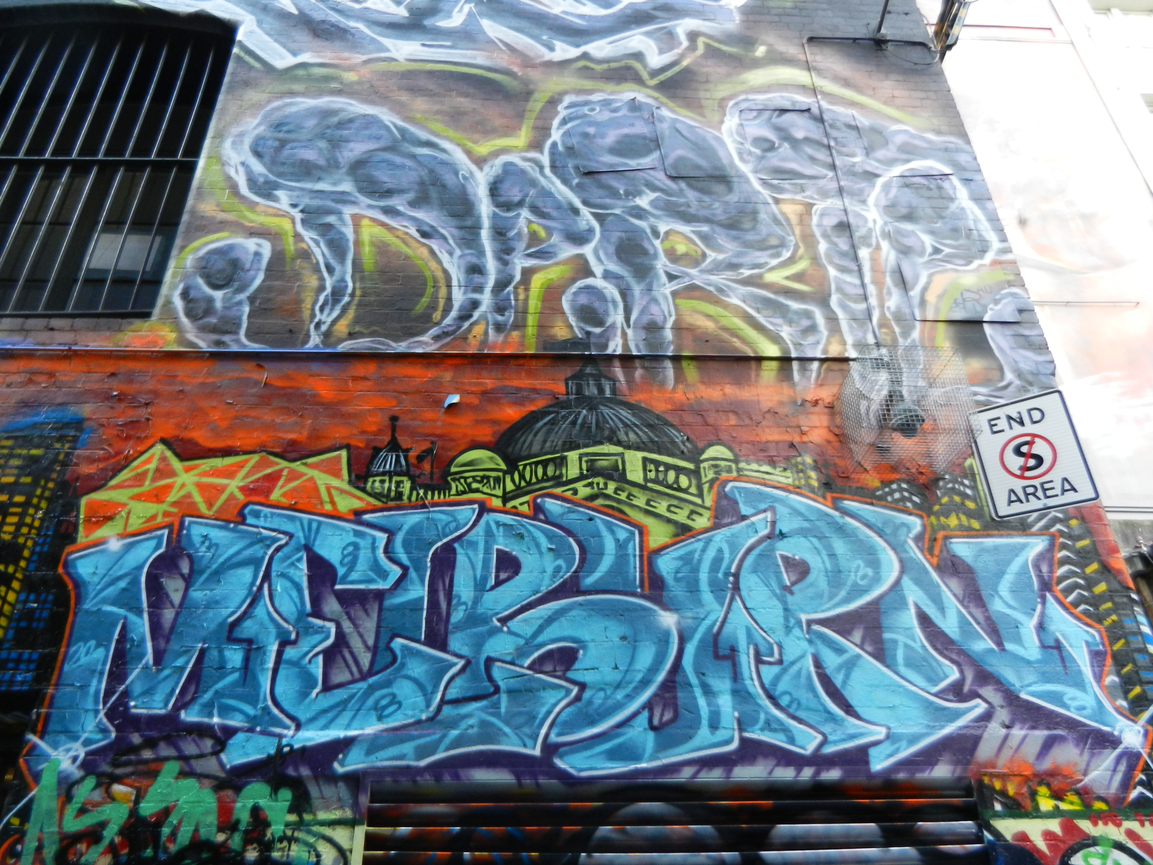 Graffiti style painting that reads Melbourne in blue paint on a yellow red, and green background.