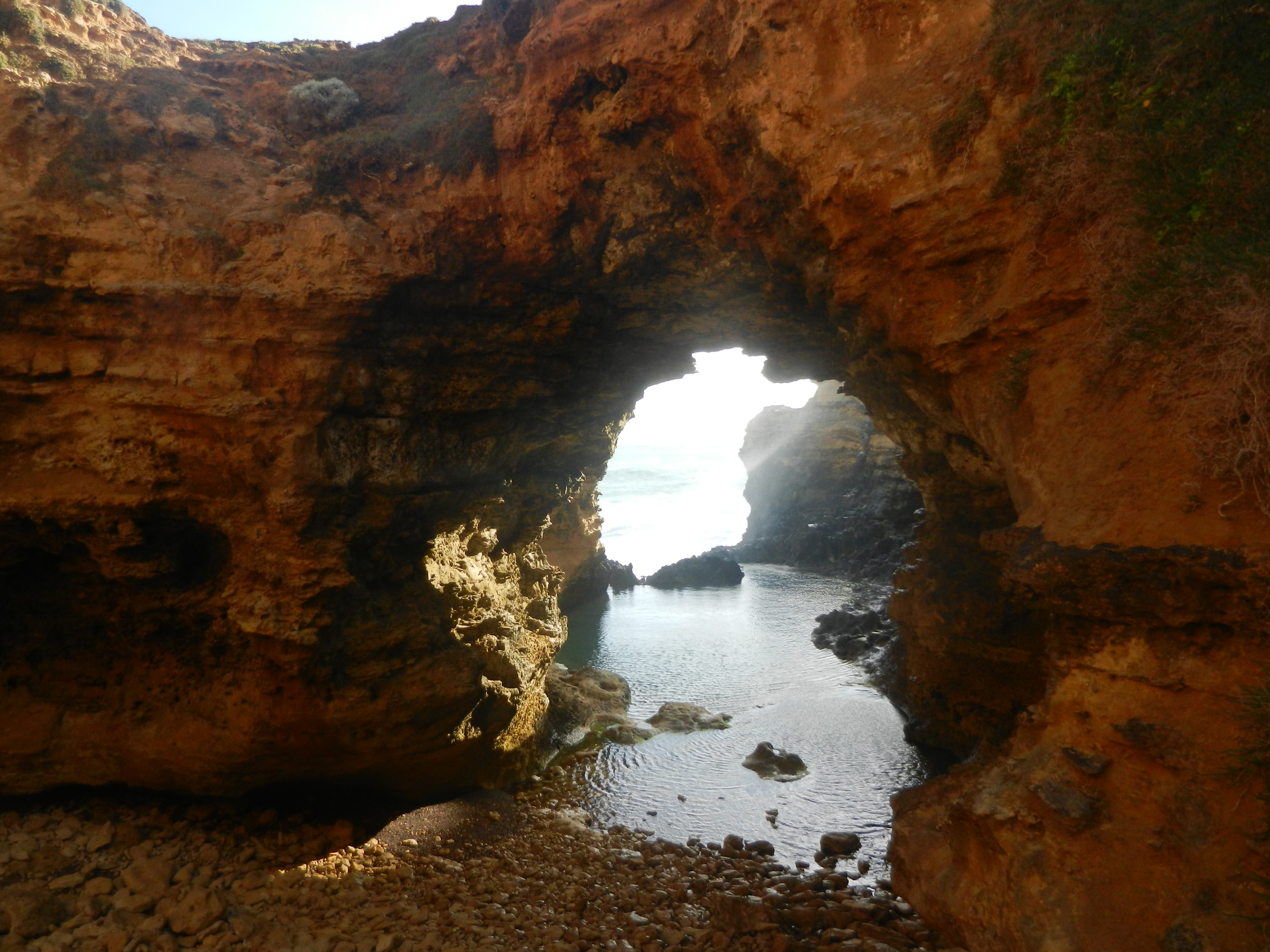 Yellow-orange colored sea arch with ocean water sitting just below.