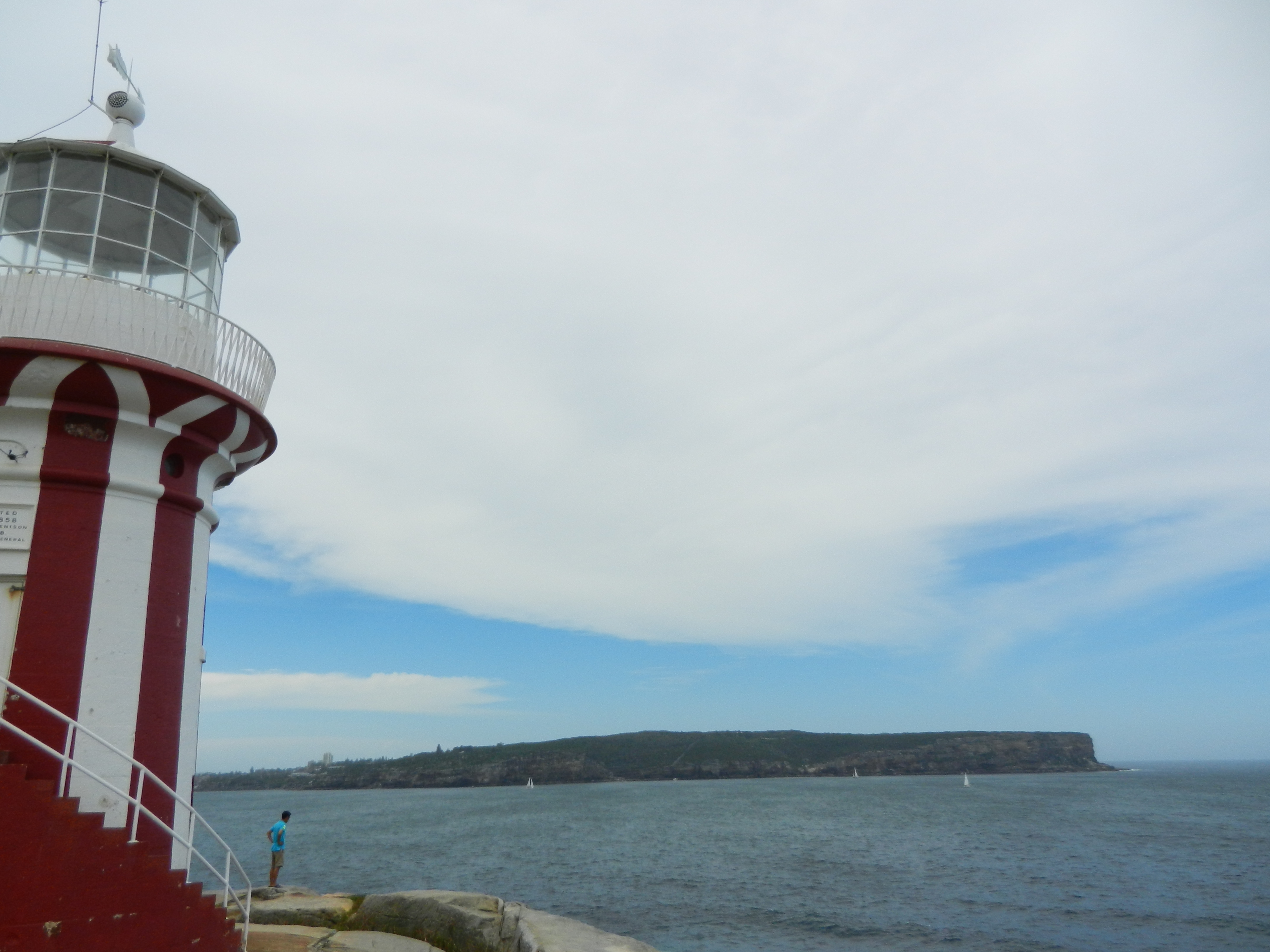 Red and white lighthouse on the left, open water on the right with an island in the background.