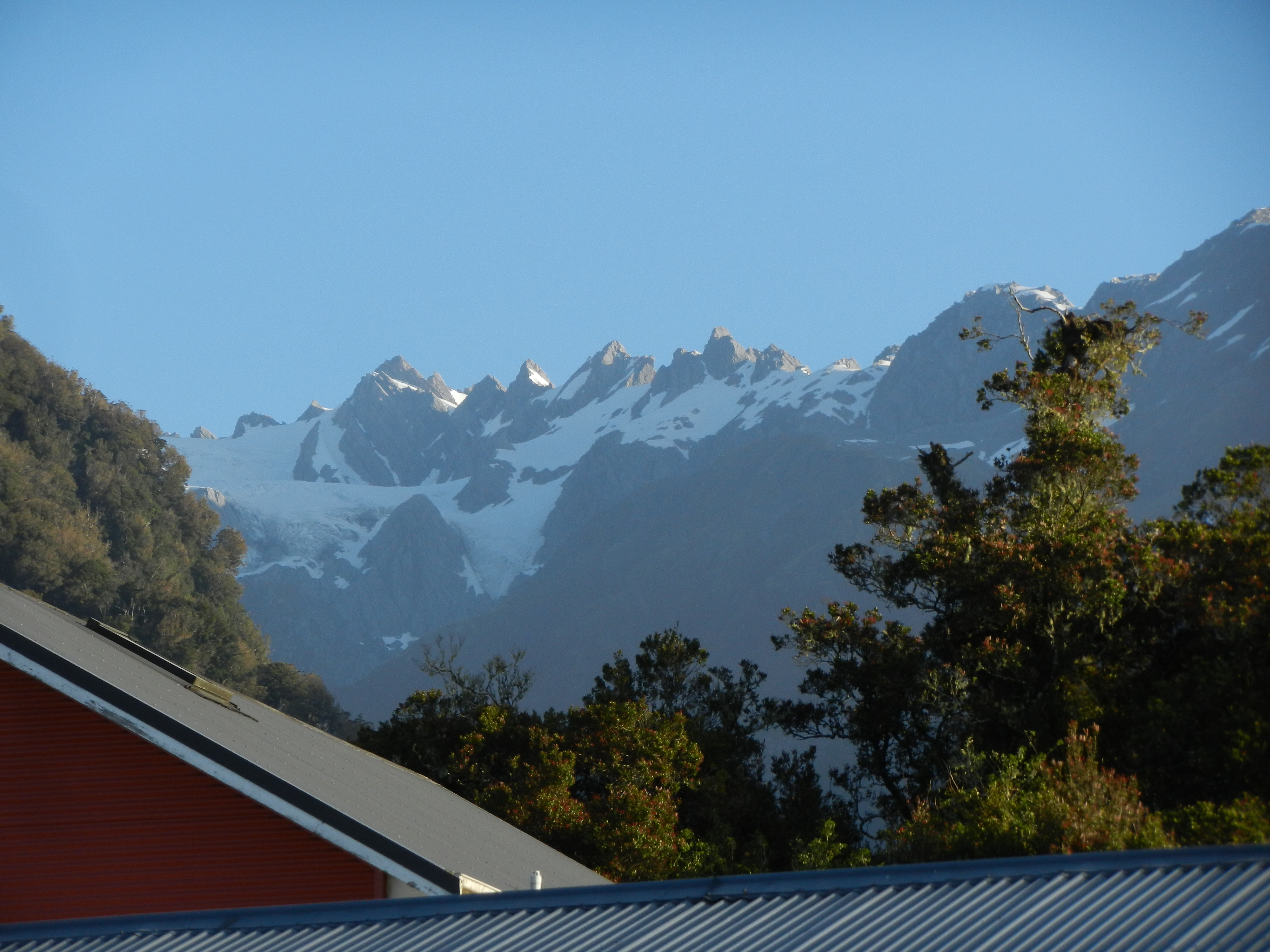 Building rooftops in the foreground with trees and glacier covered mountains in the background.