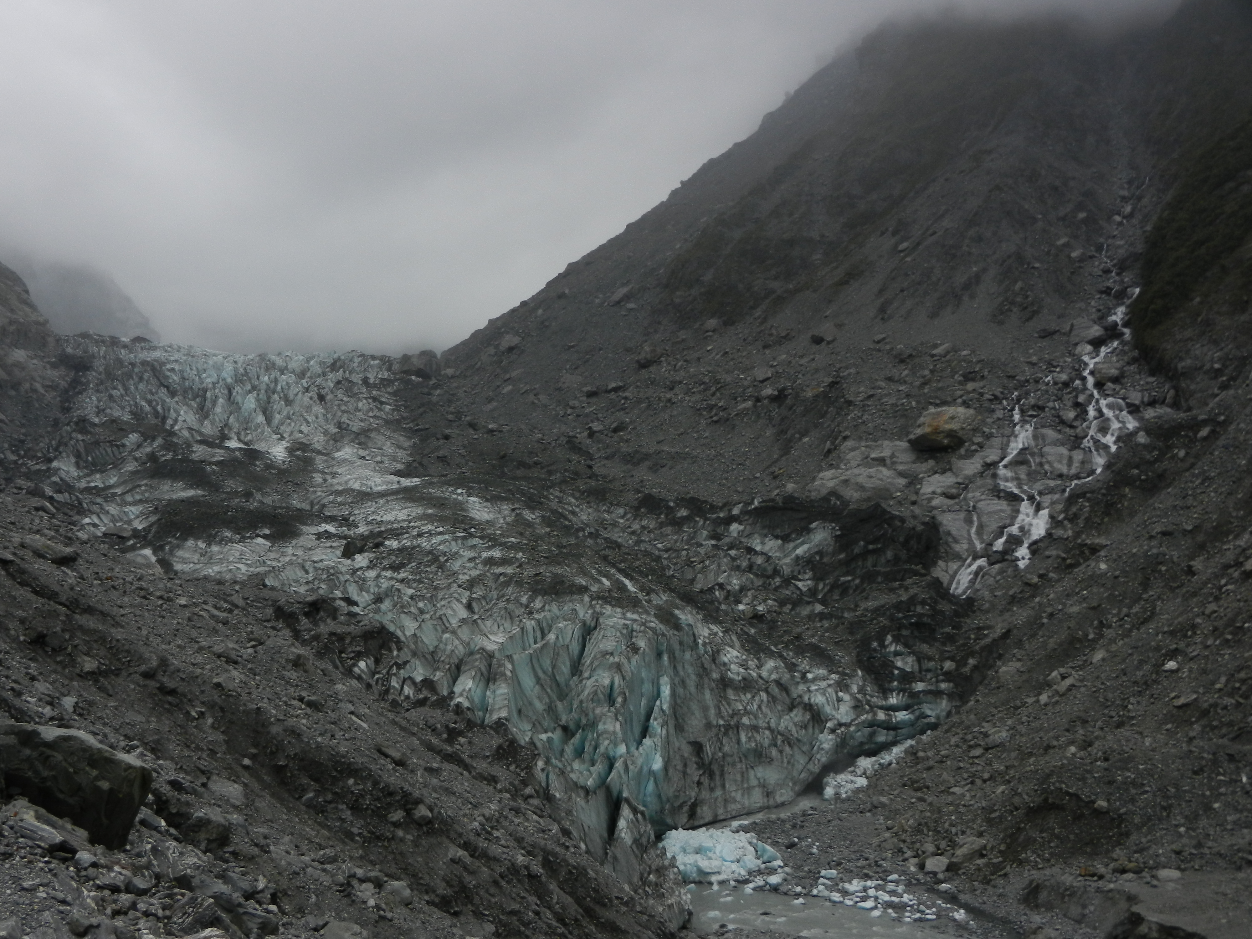 Rocky valley filled with a blue and white glacier.