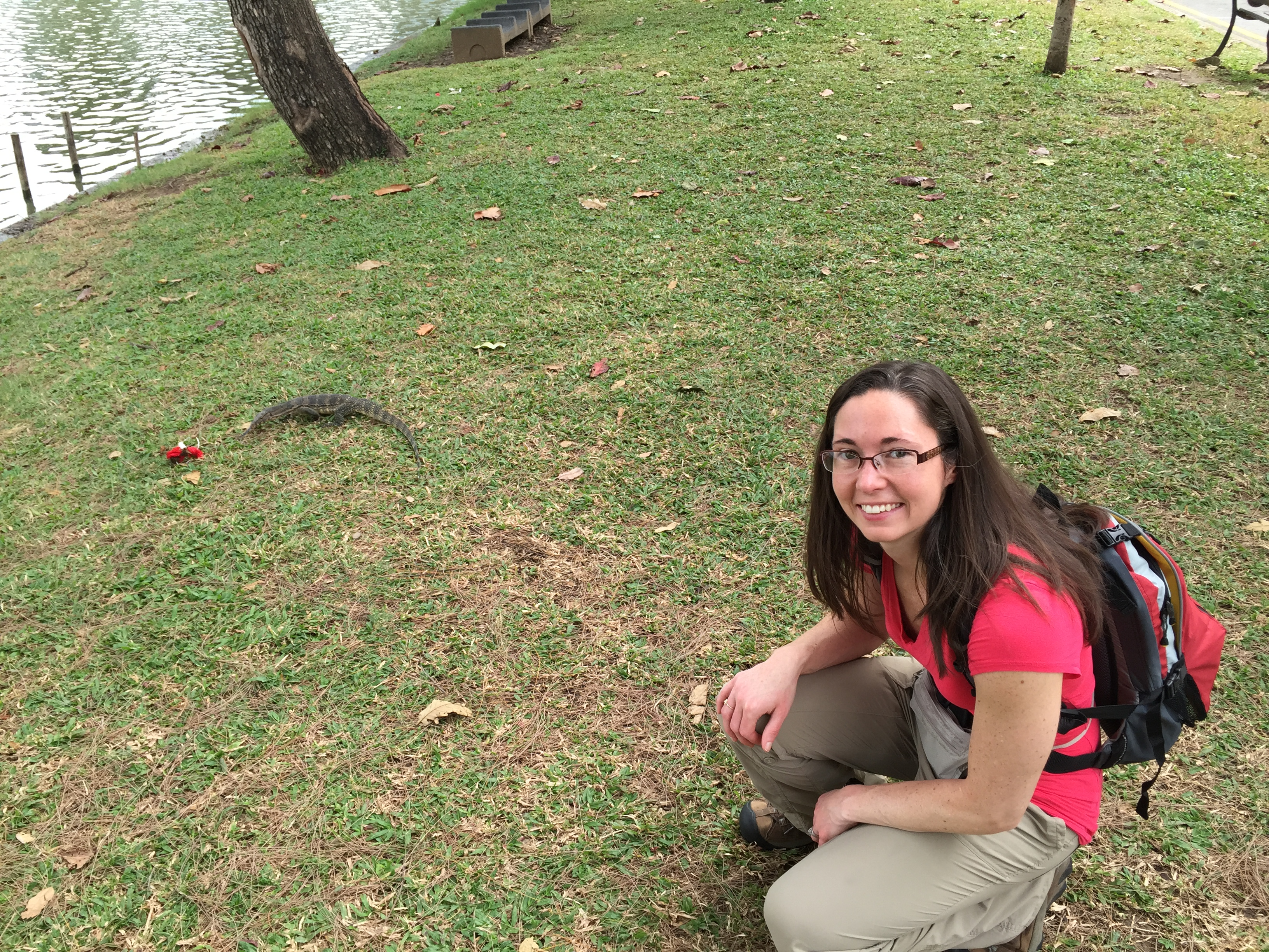 Adult female with long dark hair and glasses squatting down next to a large lizard in the grass.