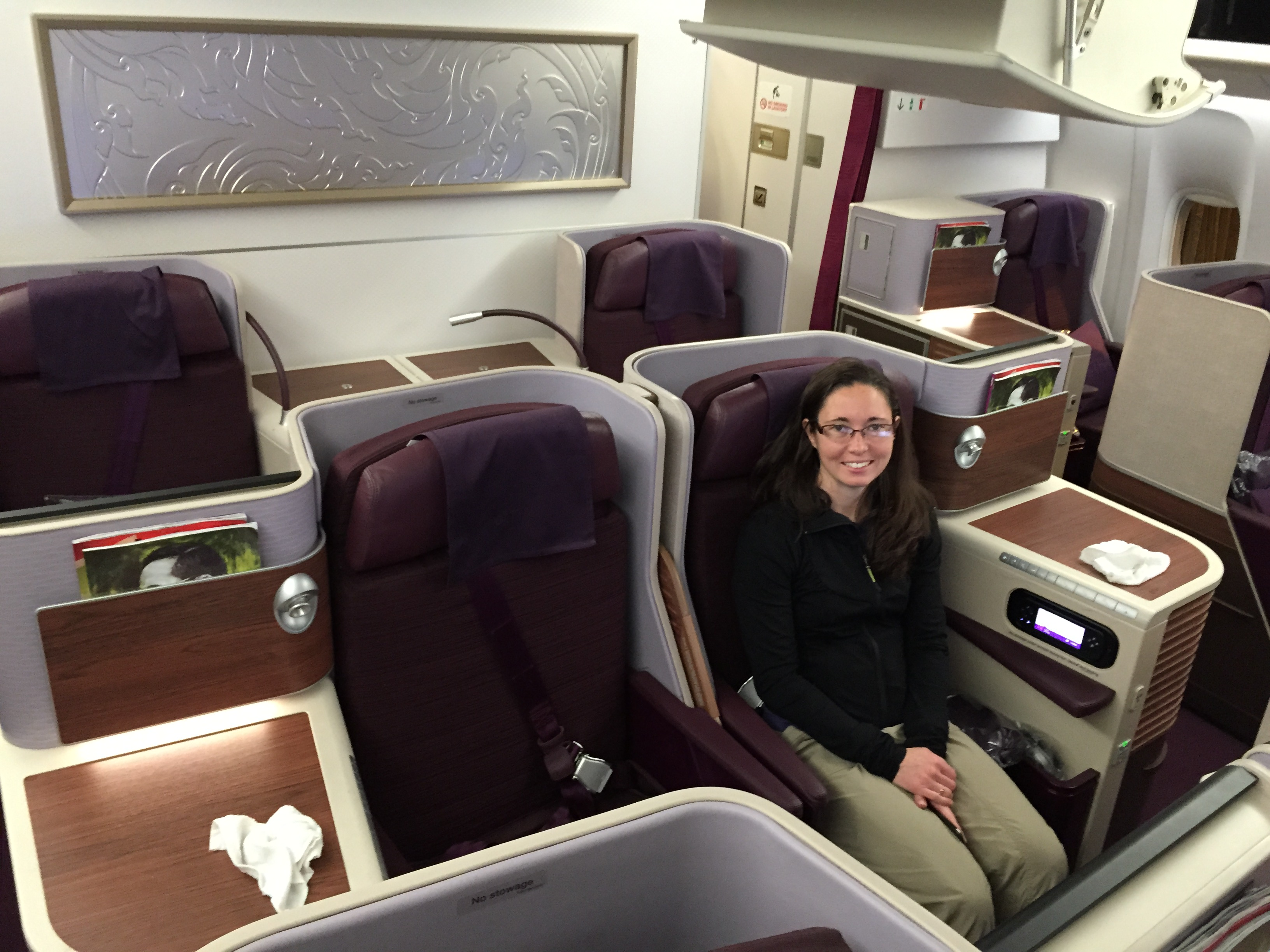 Adult female with long dark hair and glasses sitting in business class section of an airplane.