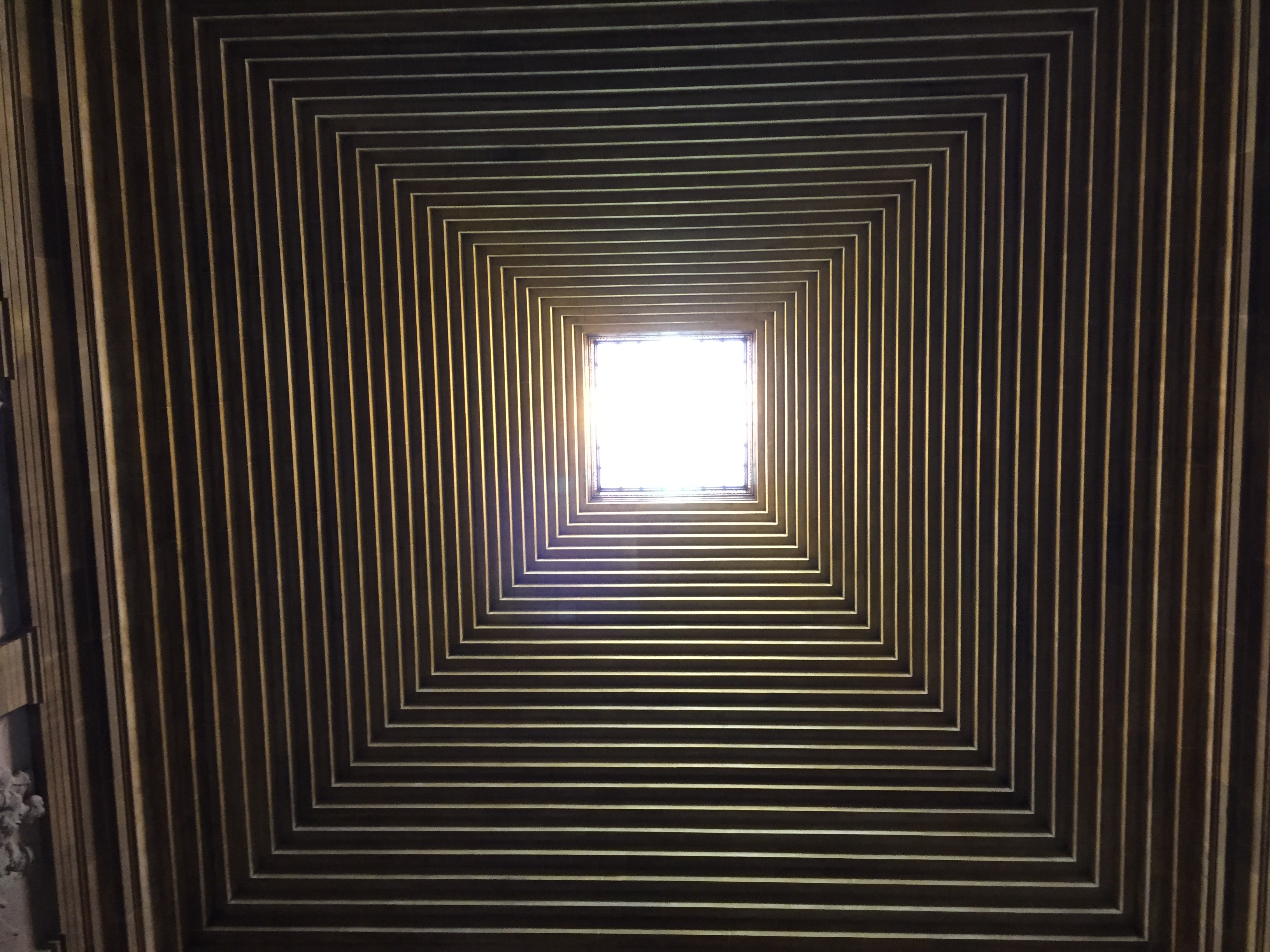 Photo looking up at a pyramid-like ceiling with a square skylight in the middle.