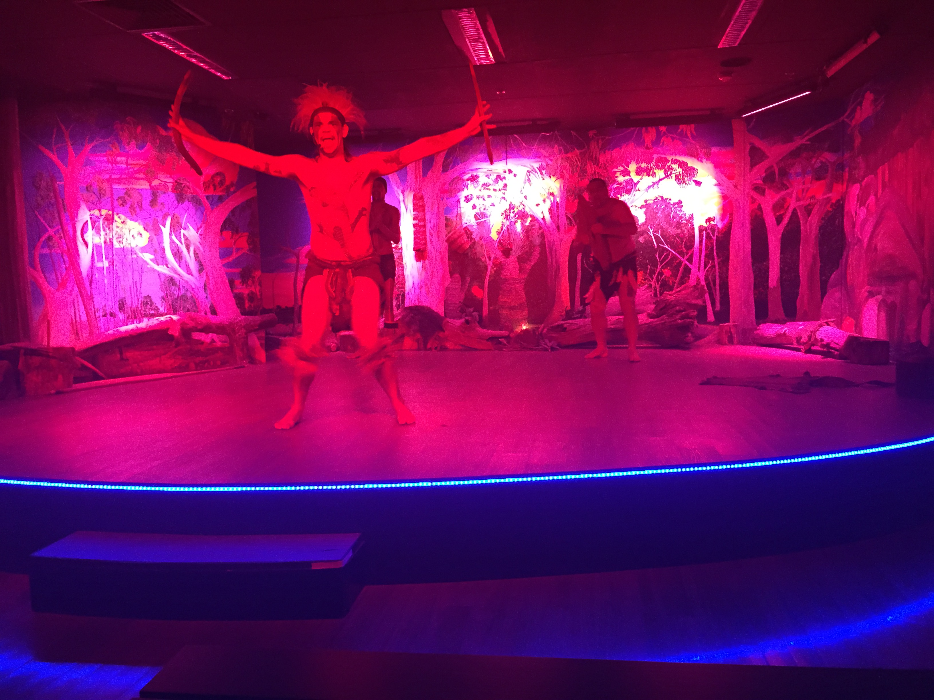 Stage with pink lighting and native Aboriginal performers.