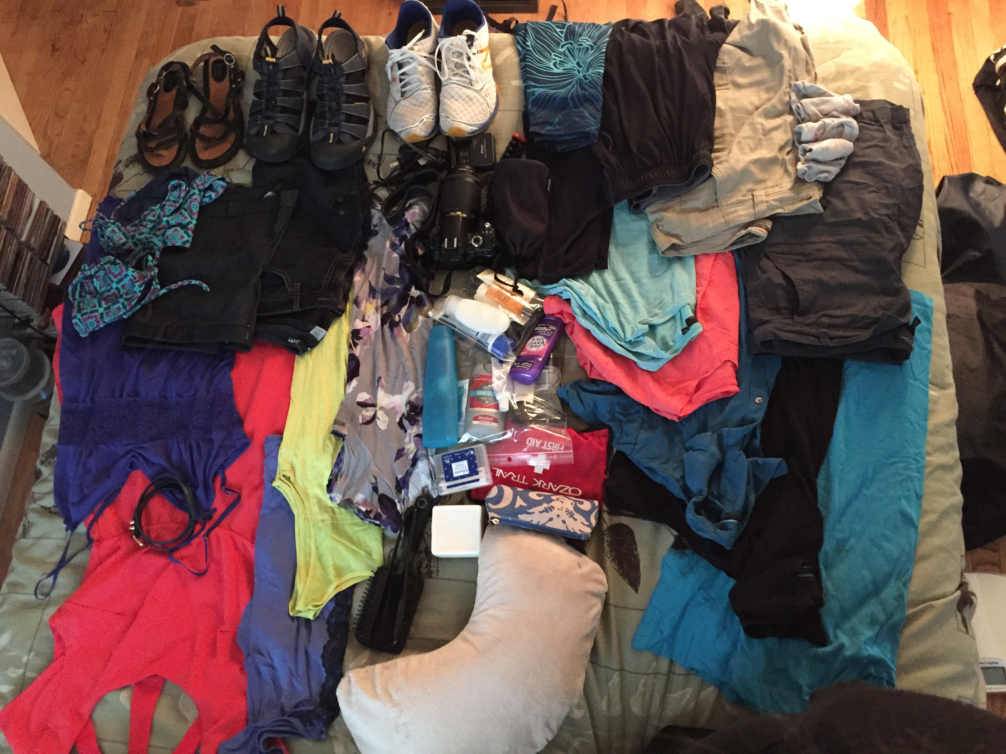 Clothes, shoes, and toiletries arranged on top of a bed.