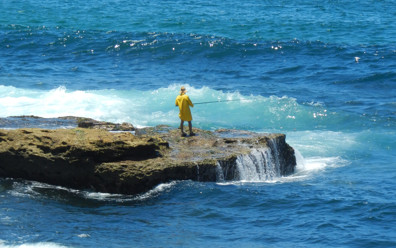 Fisherman wearing yellow rain gear standing on a rock surrounded by water.