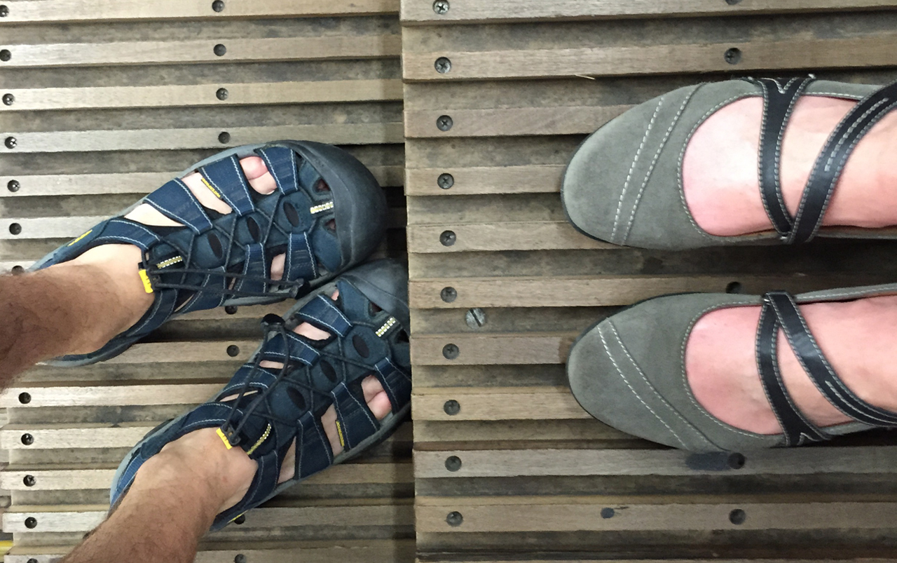 Man's feet on the left wearing dark blue sandals, woman's feet on the right wearing grey shoes standing on the wooden stairs of an escalator.
