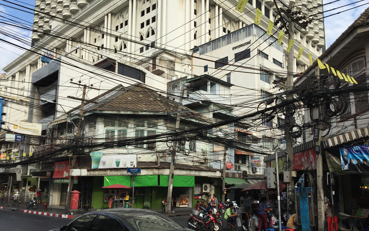 Busy street intersection with multiple electrical lines hanging above.