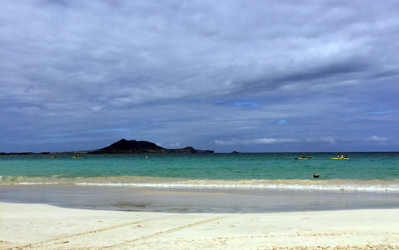 Sandy beach with turquoise ocean and an island in the distance.
