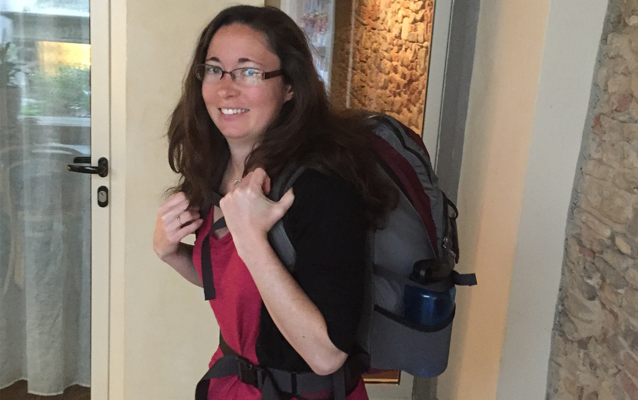 Adult female with long, dark hair and glasses standing with a backpack on her back.