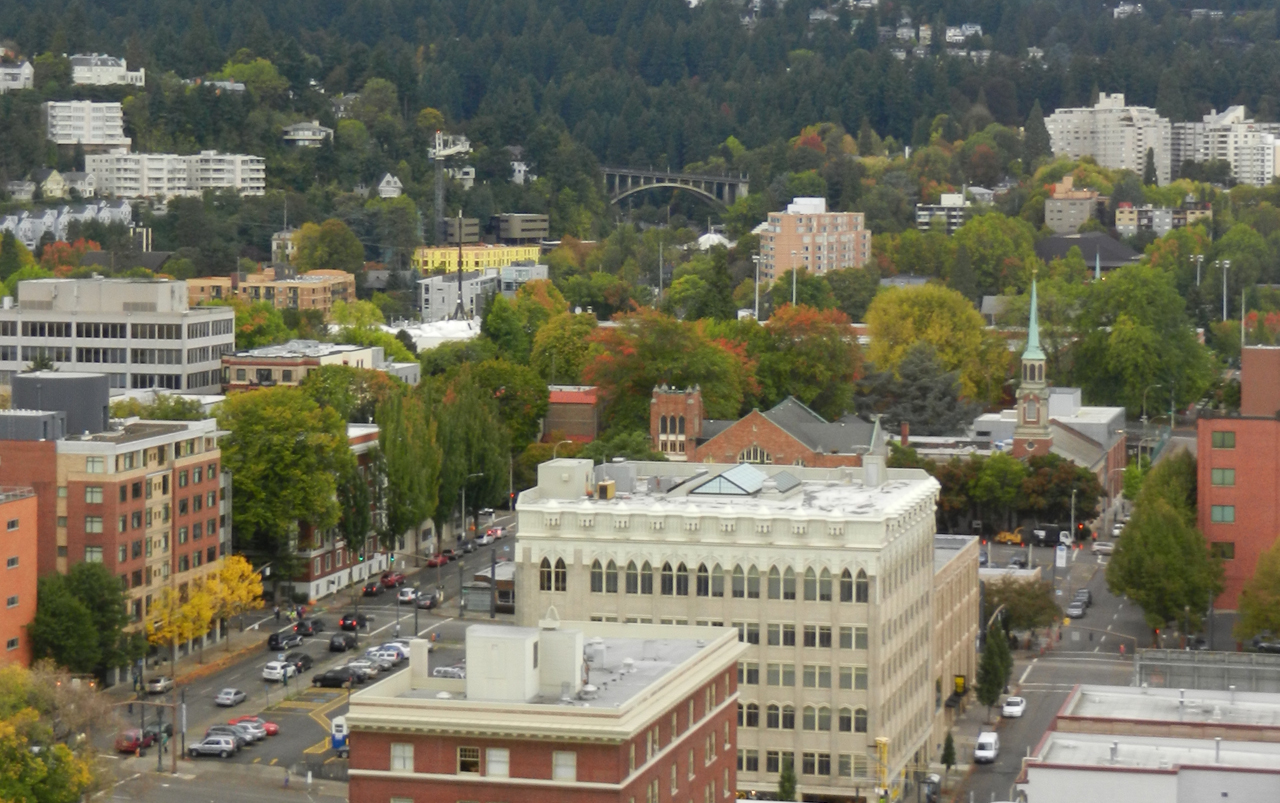 Aerial photo of downtown Portland with buildings, roads, trees, and an arched bridge in the distance.