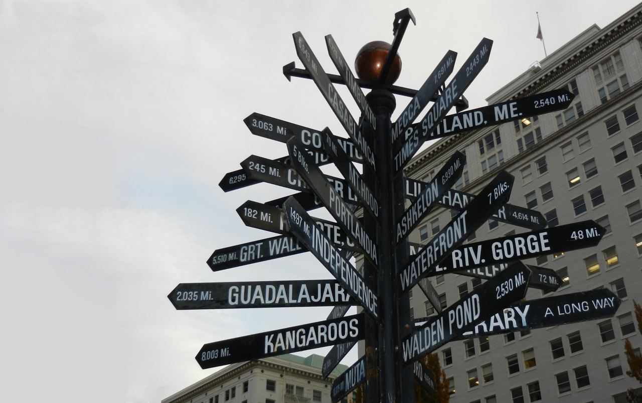 Sign with multiple destinations and their distances listed and pointing and various directions.
