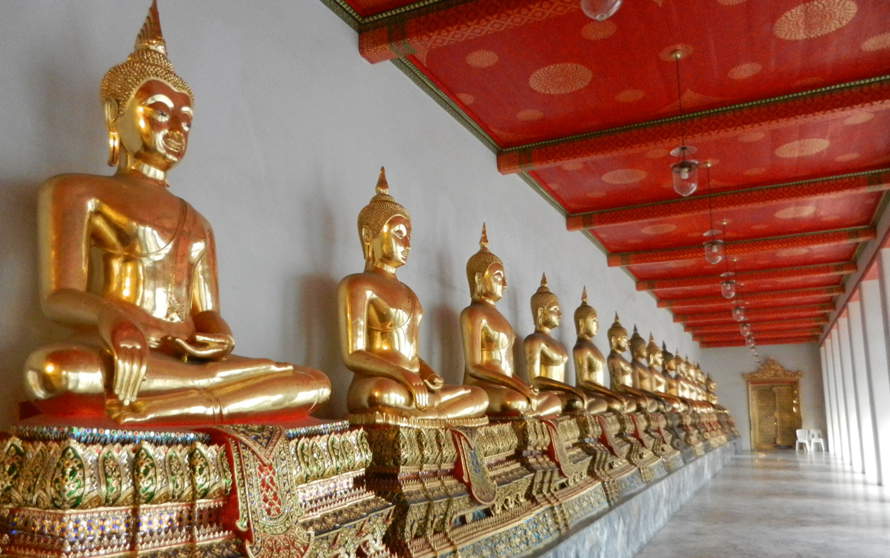 Golden Thai Buddha statues in a row side by side against a white wall with a red ceiling above.