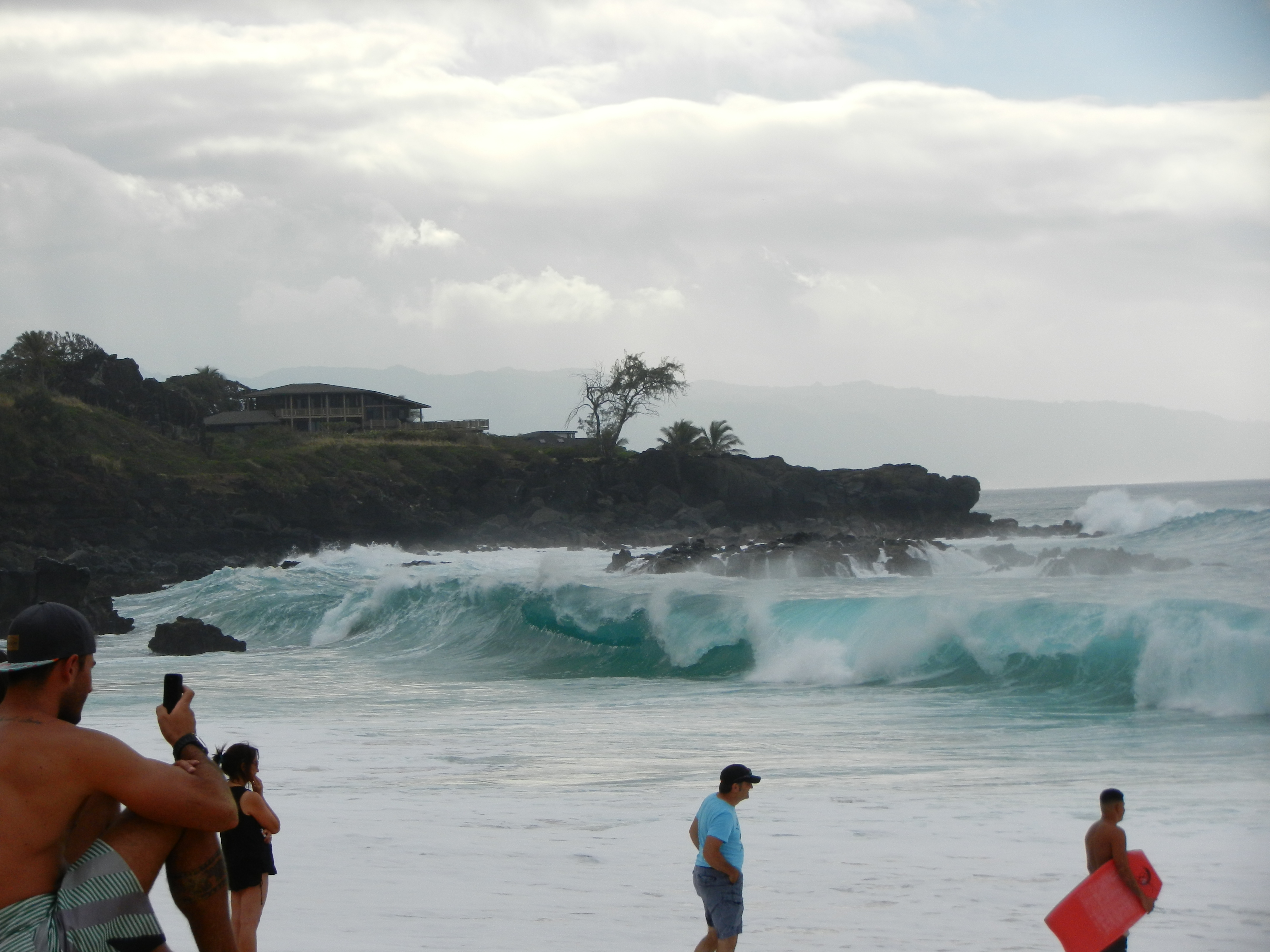 Huge ocean waves crashing onto beach in background with spectators in the foreground.