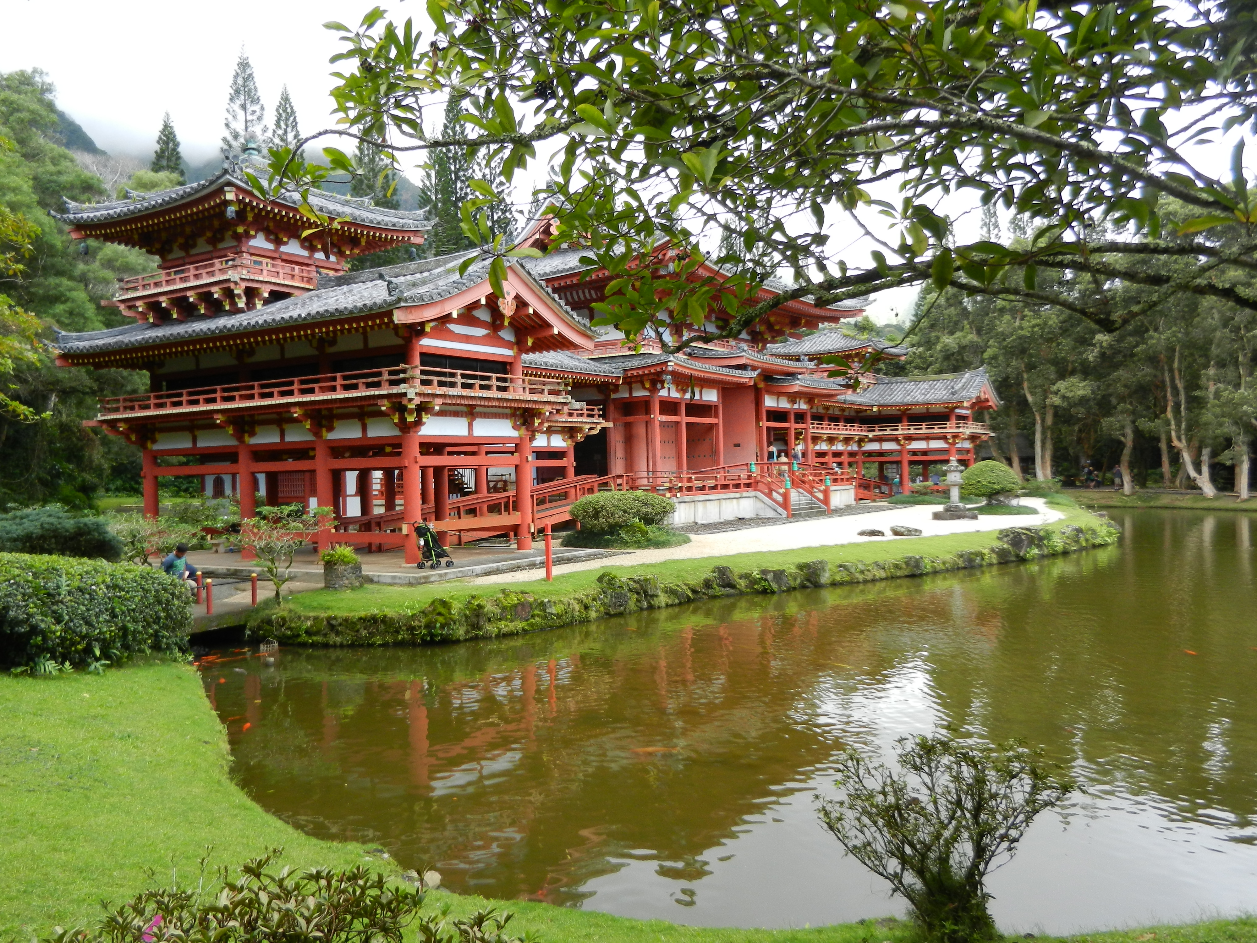 Japanese style temple in the background with a green pond and trees in the foreground
