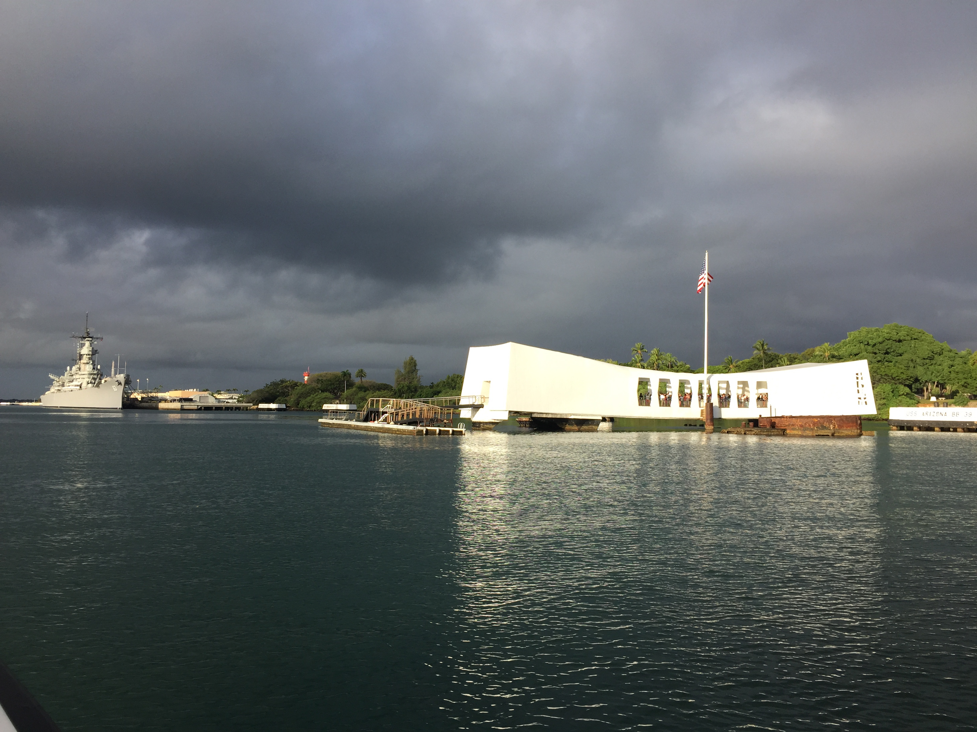 USS Arizona Memorial on the right surrounded by water.
