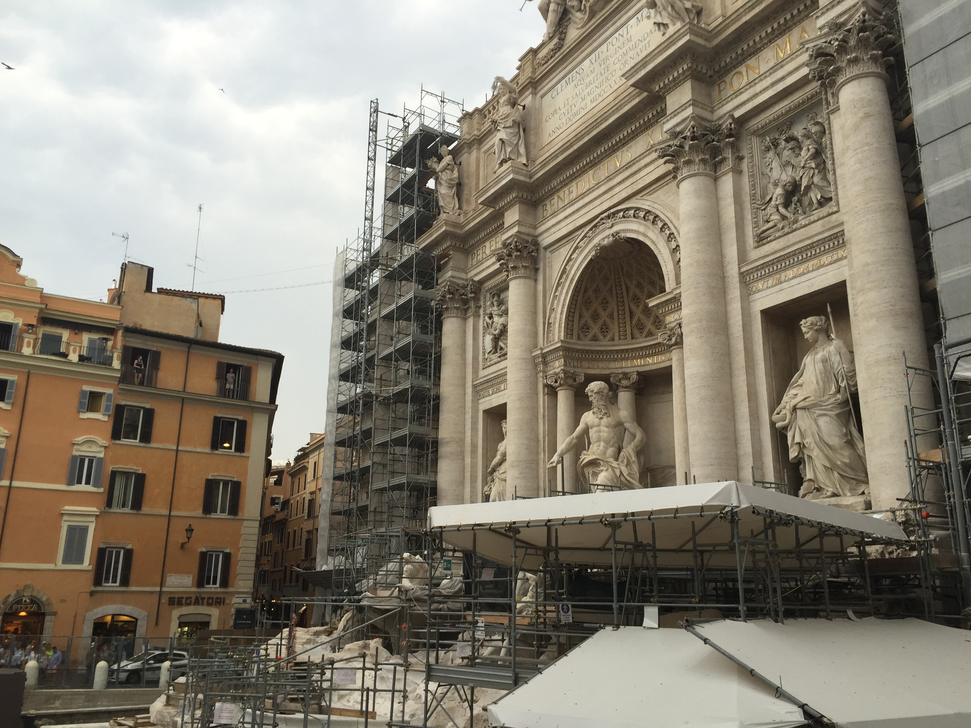 Large fountain sculpture with Roman style architecture and figurines covered in scaffolding.