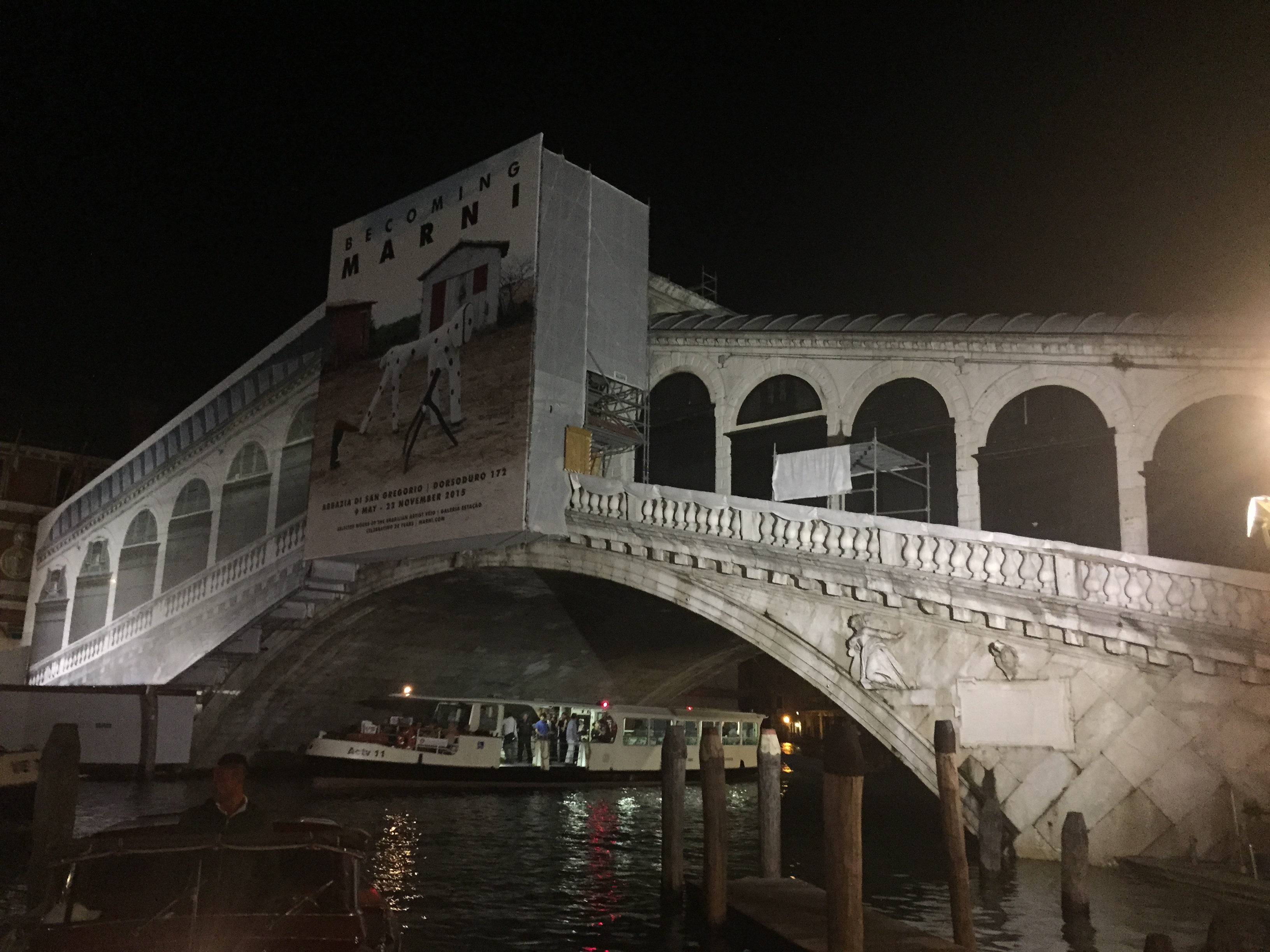 Nighttime photo of arch bridge over canal covered in scaffolding on the left side.