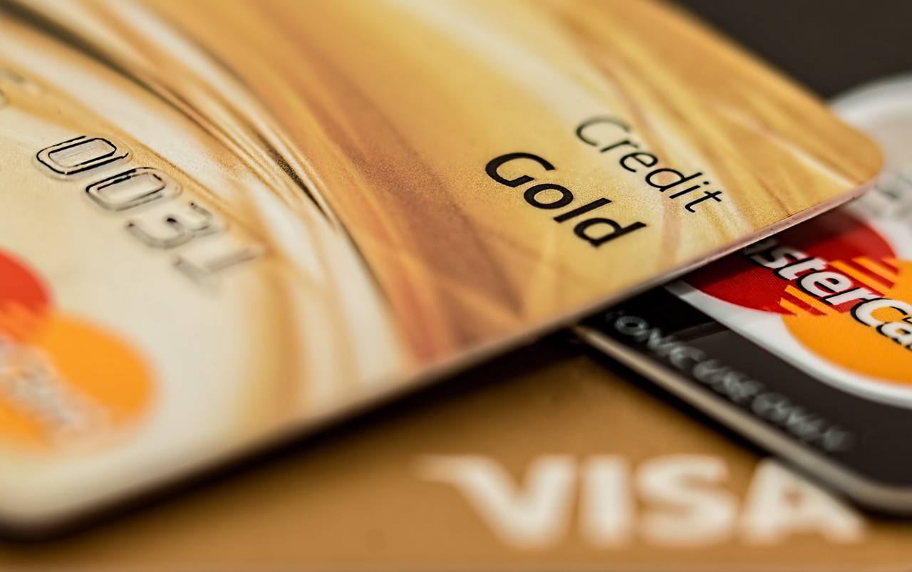 Stack of two gold colored and one black colored credit card.