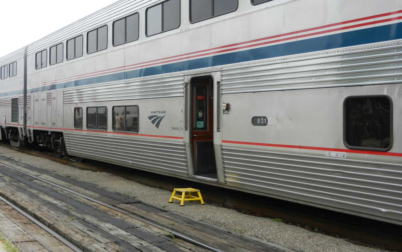 Amtrak train on the left with a yellow stepping stool outside an open door.