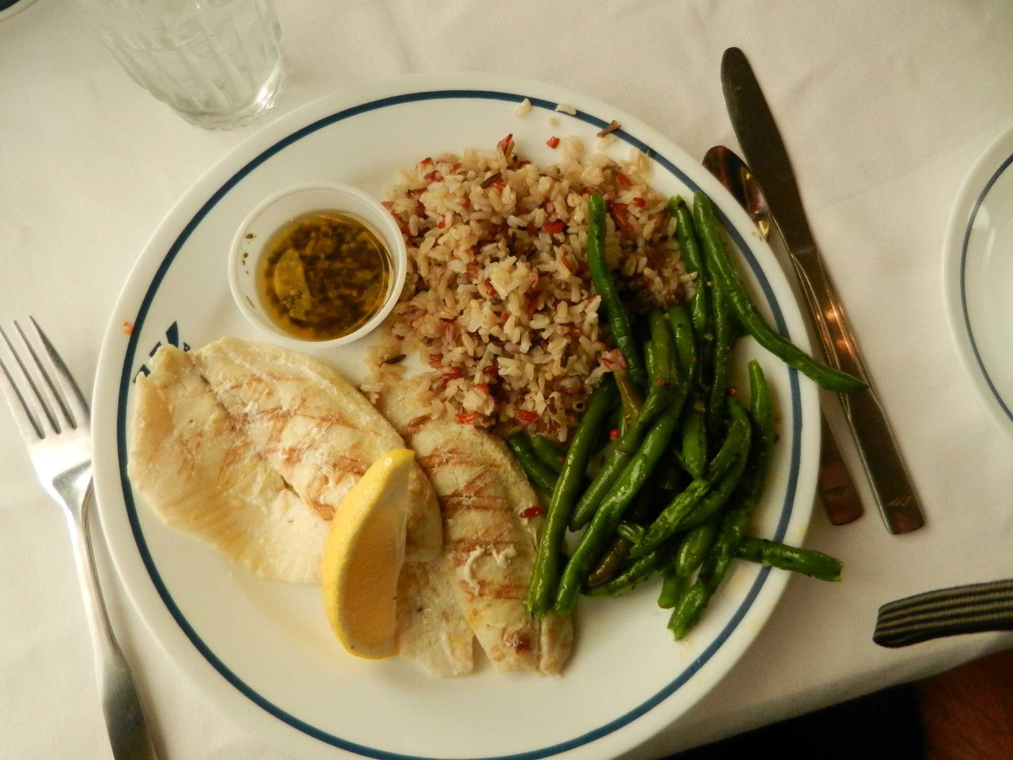 Fish with a lime wedge, brown rice, and green beans on a white plate.