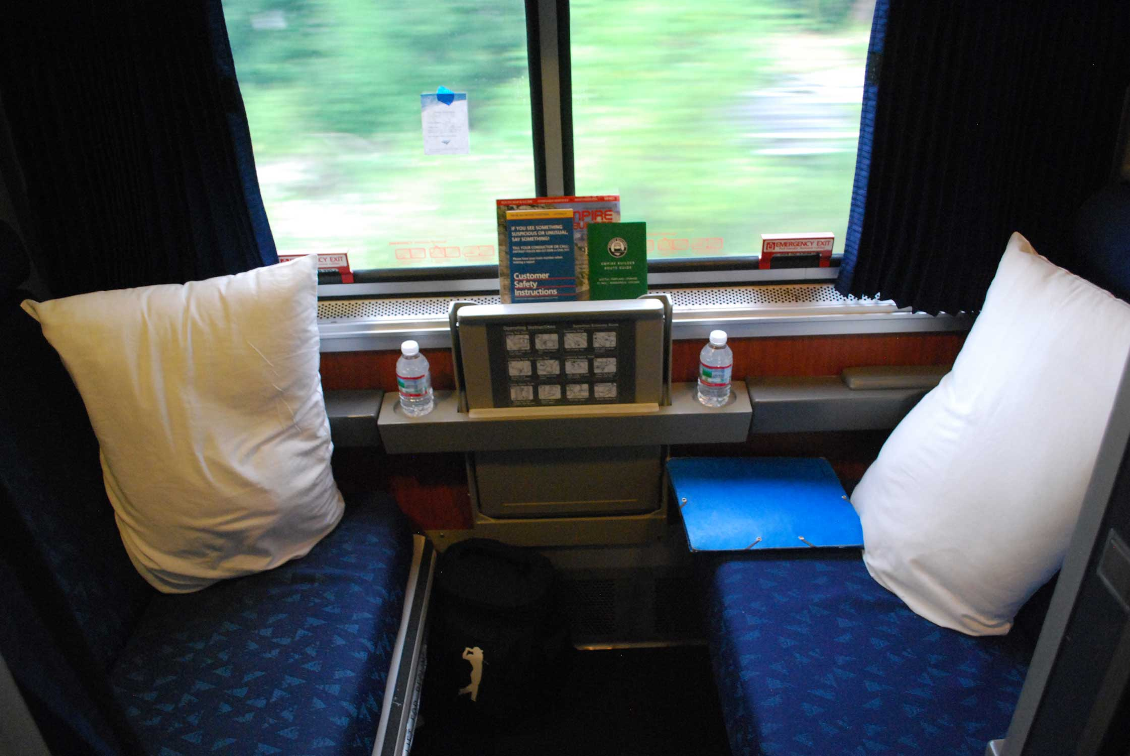 Photo looking into a small bunk room with two blue seats facing each other.