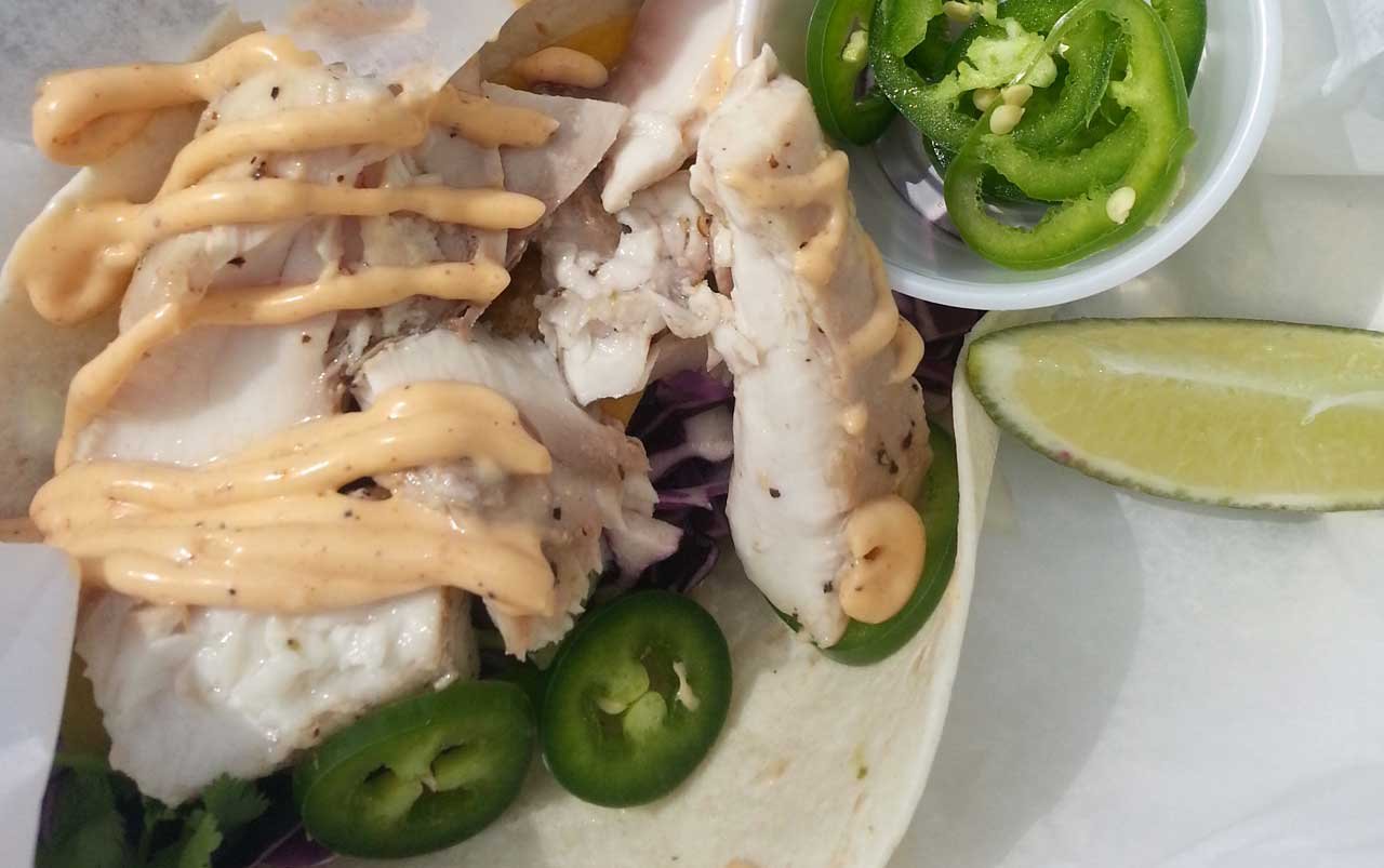 Photo of fish taco from above. Topped with light orange sauce and jalapenos, with more jalopenos and a lime wedge on the side.