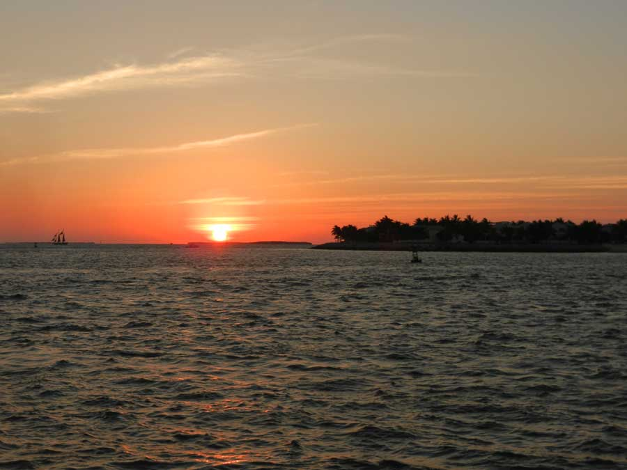 Ocean water in the foreground. Silhouette of an island on the right in the background, with sunsetting in the middle and a sailboat to the left of the sun.