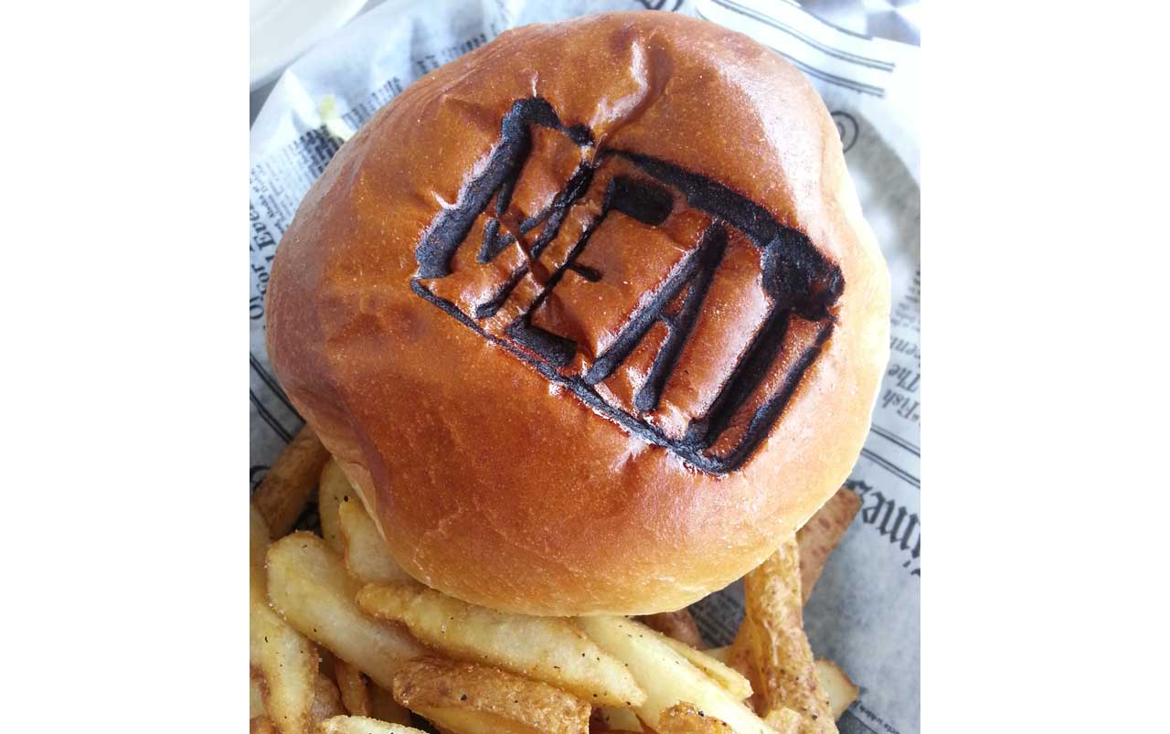 """Photo of burger and fries from above with """"MEAT"""" stamped on the top of the burger bun."""