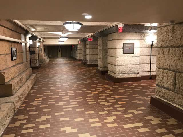 Underground space with multicolored brick floor and limestone columns.