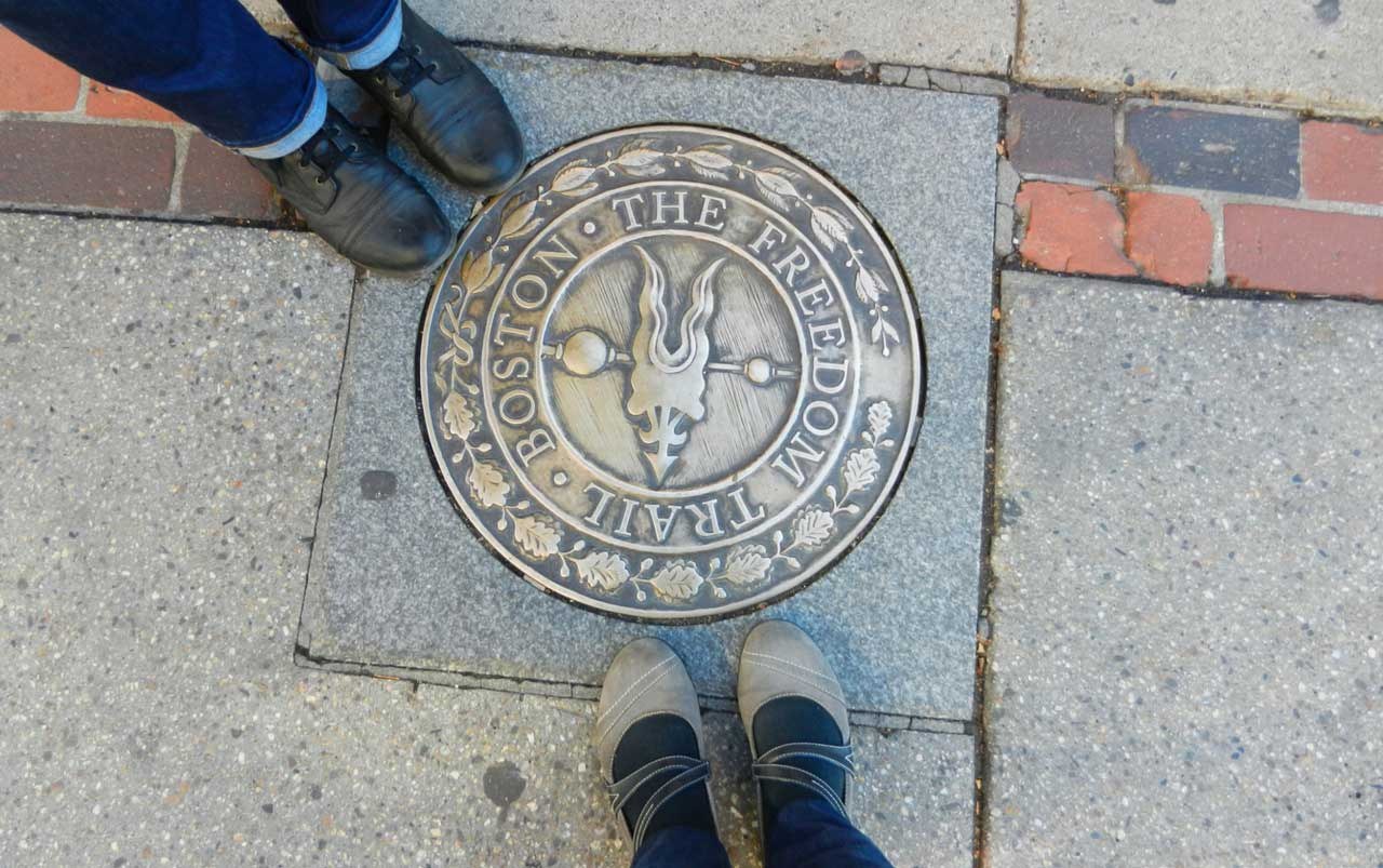 """Two sets of women's feet standing around a gold colored medallion that reads """"Boston, The Freedom Trail""""."""