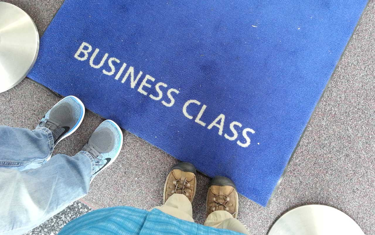 """Man's feet on the left wearing blue tennis shoes, women's feet on the right wearing brown hiking boots standing next to a dark blue rug with the words """"Business Class"""" on it in white."""
