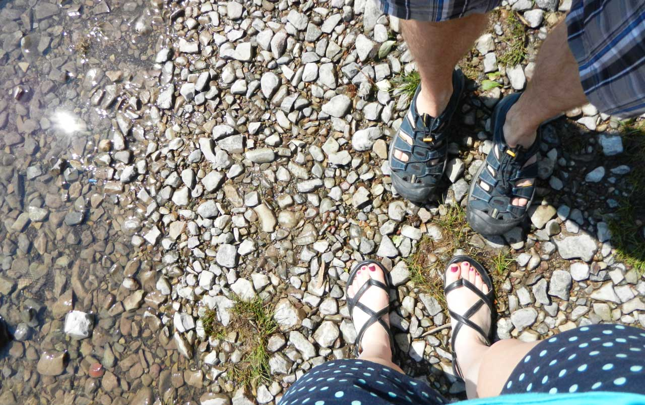 Woman's feet wearing black sandals at the bottom, man's feet wearing dark blue sandals at the top surrounded by grass and rocks.