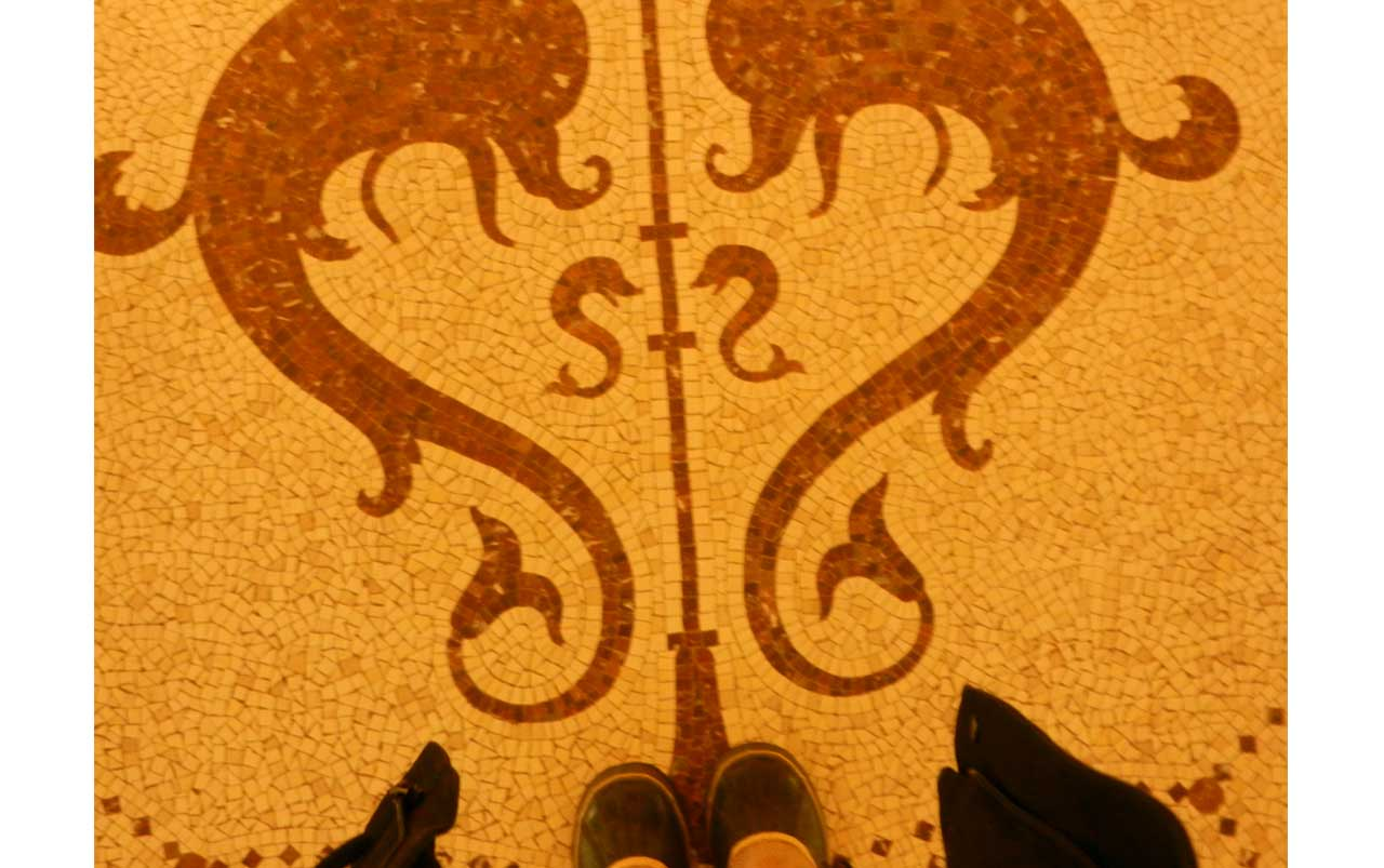 Woman's feet wearing brown winter boots at the bottom, standing on a mosaic floor with a red pattern of two large dolphins enclosing two smaller dolphins with a vertical line bisecting the composition.